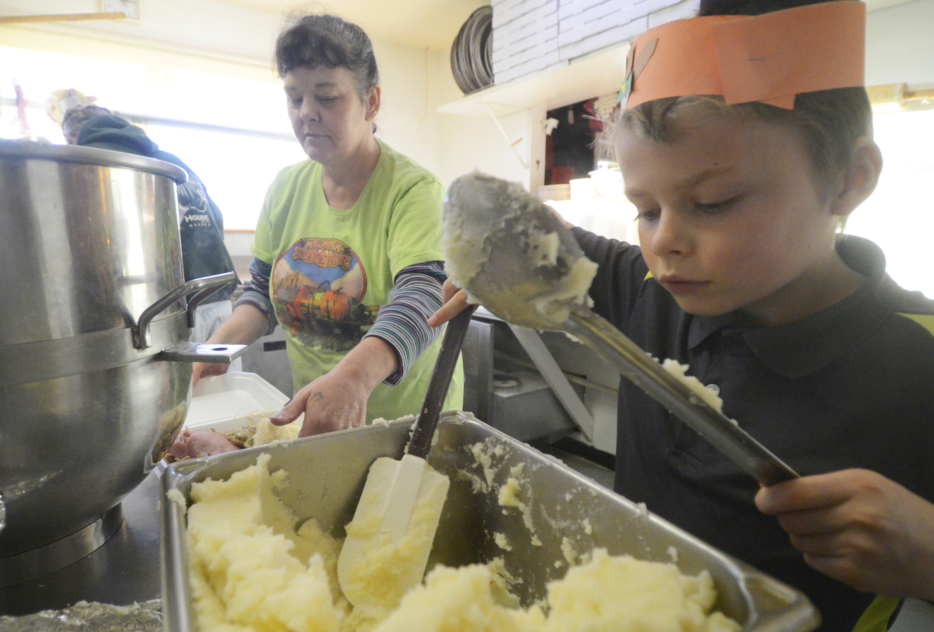 Dalton Goodnight serves up mashed potatoes at Charlie's Pizza in Nikiski for free meals the restaurant delivers to residents on Thanksgiving day Thursday, Nov. 27, 2014, in Nikiski Alaska. Owner Steve Chamberlain said Felix Martinez, owner of M & M Supermarket in Nikiski, donates a dozen turkeys every year for the holiday.