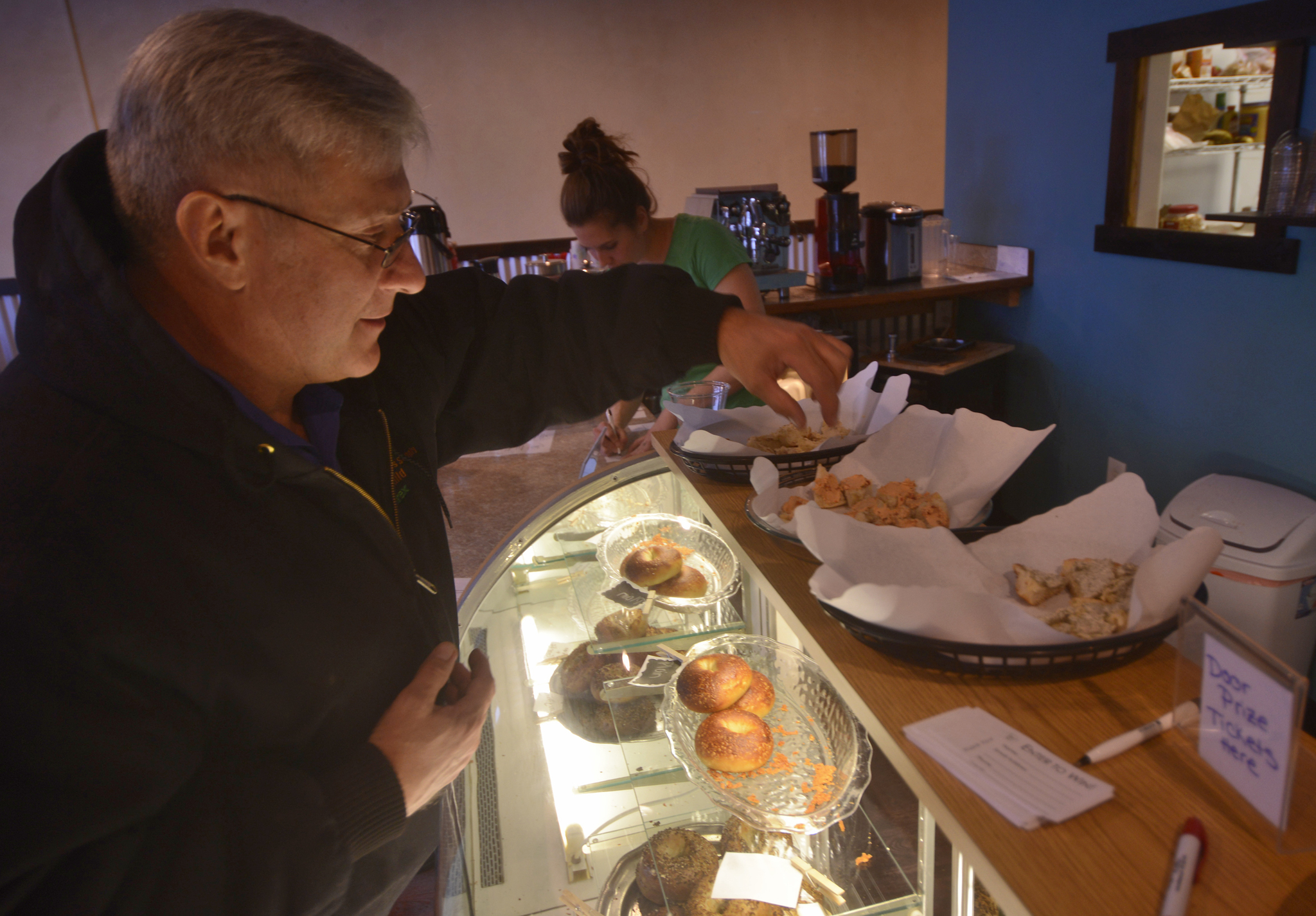 """Jeff Warton samples three flavors of bagel spread at the grand opening of the Kenai location of Everything Bagels on Tuesday, Jan. 31,2017 in Kenai, Alaska. The grand opening comes 13 days after the Kenai shop had its soft opening on Jan. 18, seven months after Everything Bagels opened its first location in Soldotna on July 15, 2016, and on the one-year anniversary of co-owners Matt and Pamela Parker (with Brooke and John Campbell) making their first batch of bagels in their home kitchen, Pamela Parker said. """"We came from Florida, where all the New Yorkers go to retire, so there's tons of delicious bagels there,"""" she said. """"We wanted to bring that up here."""" (Ben Boettger/Peninsula Clarion)"""