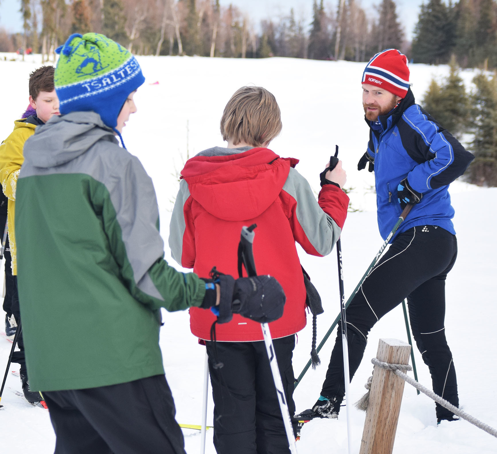 Tsalteshi Trails Youth Ski Program coach Darin Markwardt (red hat) quizzes a group of young skiers, Jan. 28 at the Kenai Golf Course. (Photo by Joey Klecka/Peninsula Clarion)