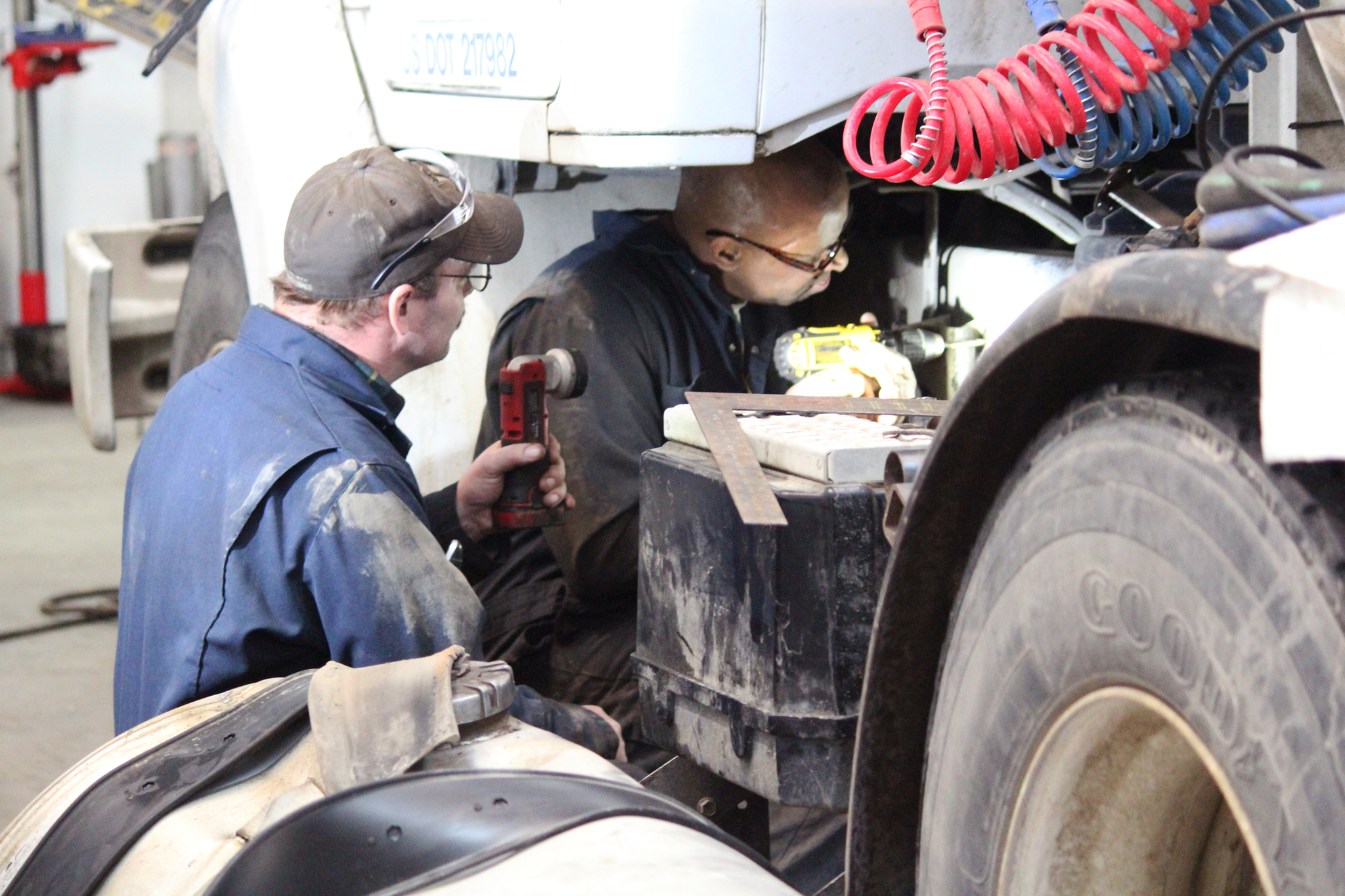 Lee Berzanske, owner of Lee's Heavy Equipment Repair, shines a light on an Enstar Natural Gas Co. truck so Thaddeus Lewis can see where to drill holes during their work day Thursday, Feb. 16, 2017 at the repair shop on Kalifornsky Beach Road near Kenai, Alaska. Lewis, an inmate at Wildwood Correctional Complex, was the first offender admitted into the facility's new Vocational Work Release Program. (Megan Pacer/Peninsula Clarion)
