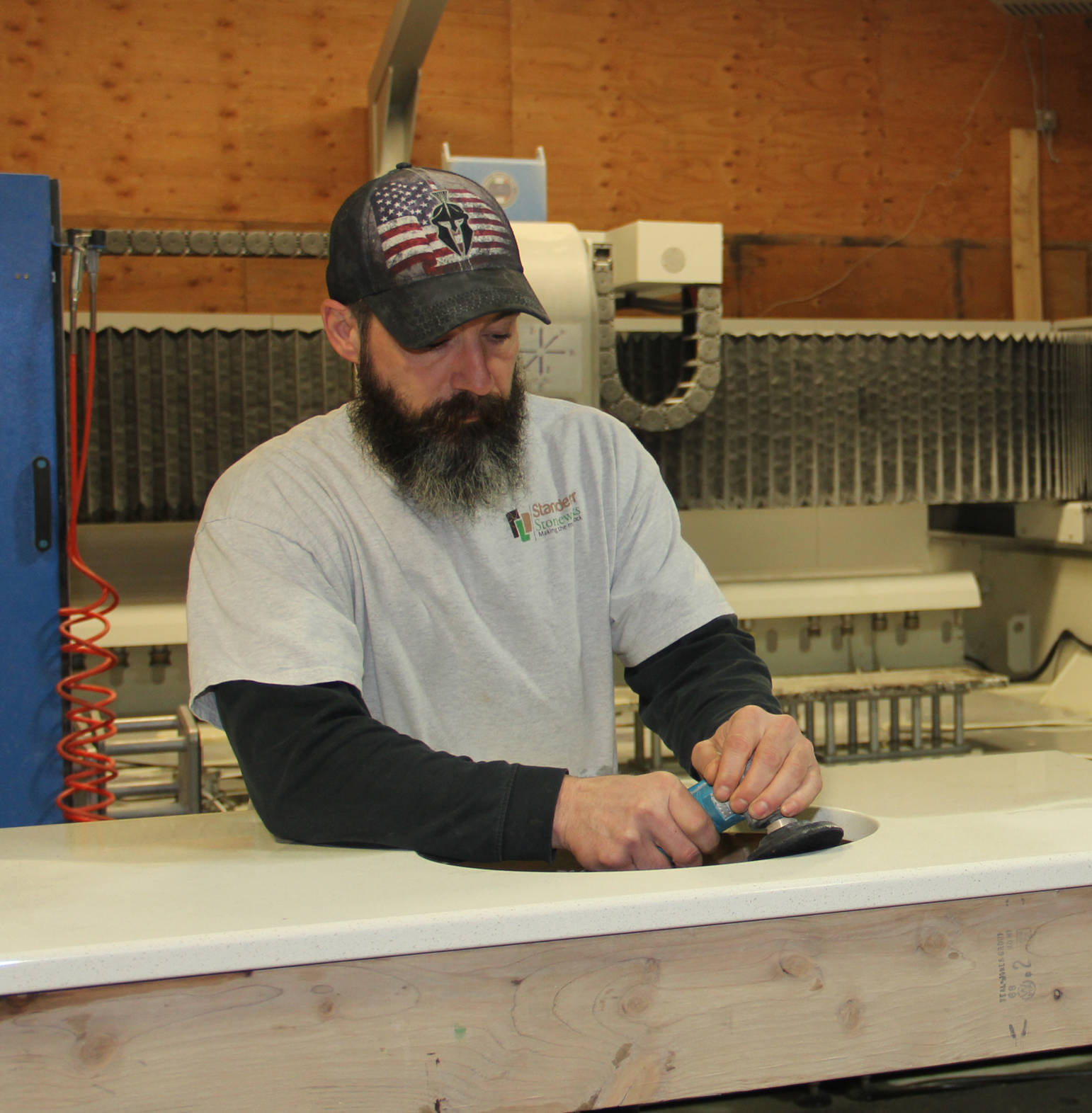 Foreman Nick polishes an undermount sink cut out on a quartz vanity at Standerfer Stoneworks.