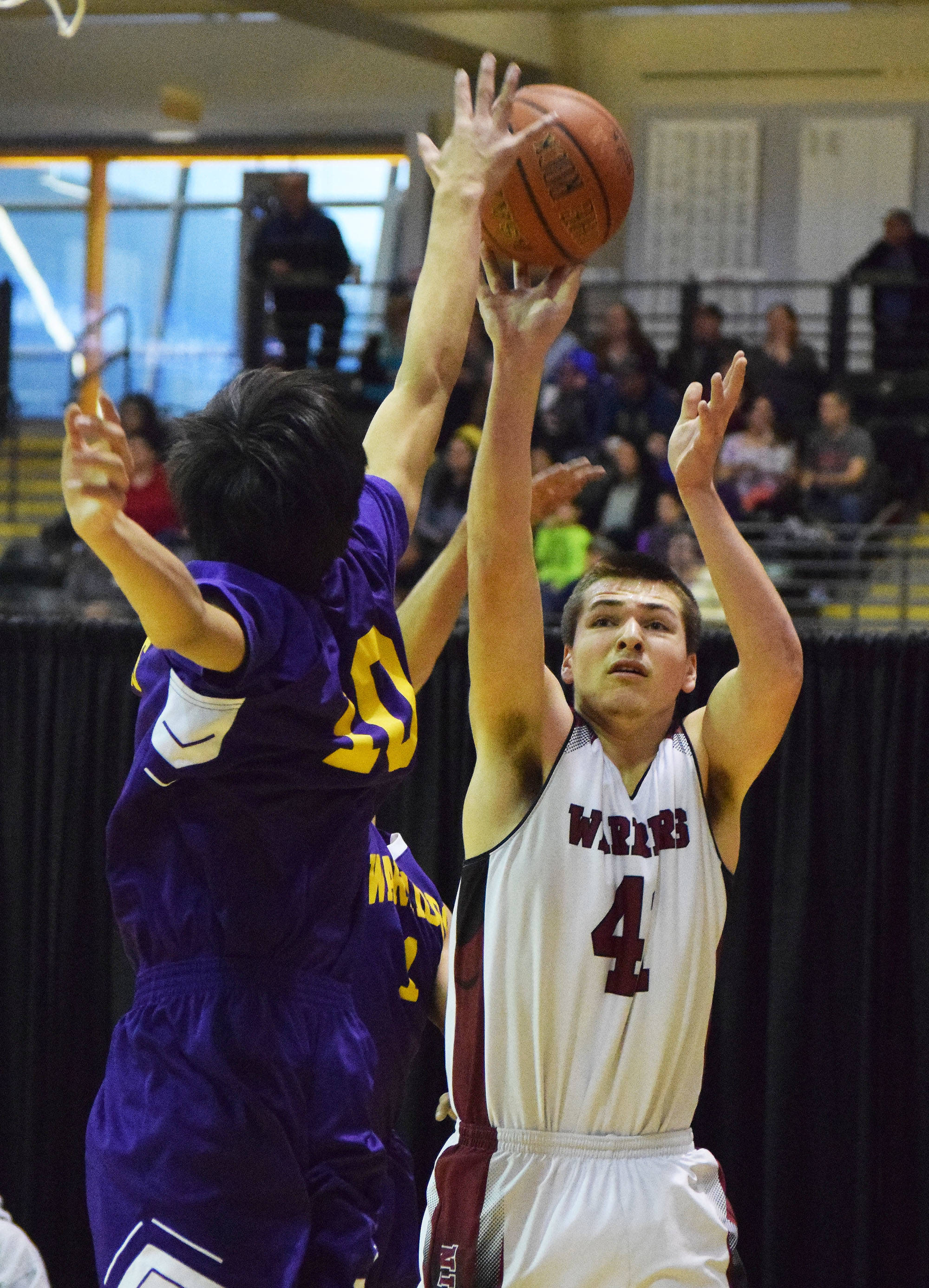 Nikolaevsk's Michael Trail shoots with Hydaburg defender Mike Eaglestaff blocking Friday, March 17, 2017, at the Class 1A state tournament held at the Alaska Airlines Center in Anchorage. (Photo by Joey Klecka/Peninsula Clarion)