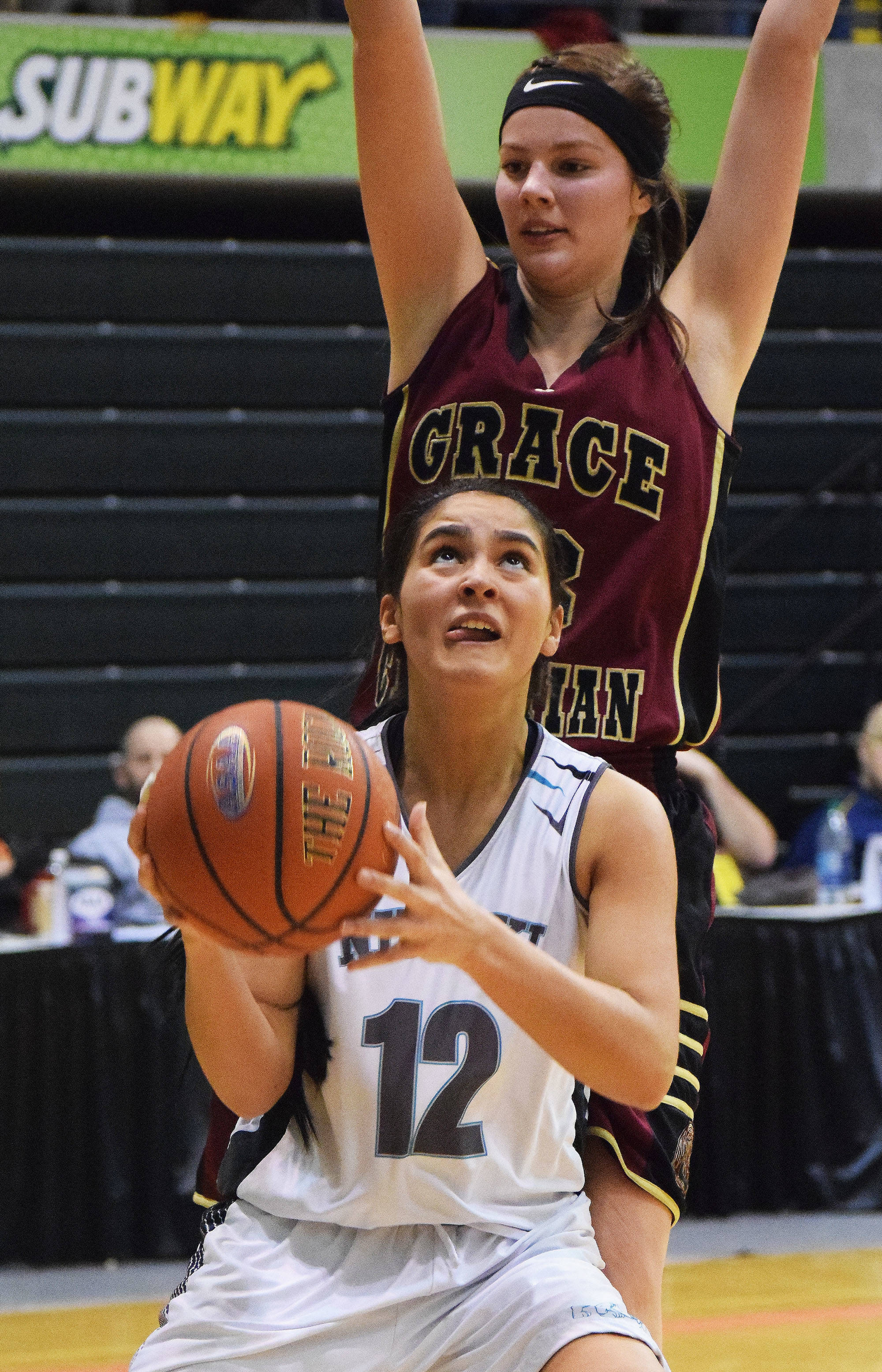 Nikiski's Brianna Vollertsen (12) looks for a shot against Grace Christian's Makenna Shamburger in the Class 3A state quarterfinal contest Thursday, March 23, 2017, at the Alaska Airlines Center in Anchorage. (Photo by Joey Klecka/Peninsula Clarion)