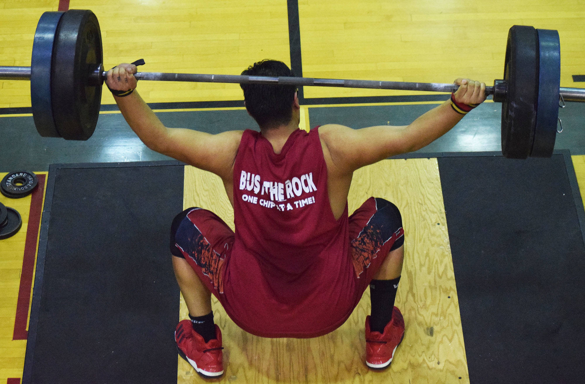 Kenai Central senior Jonathan Delgado attempts a lift Wednesday evening at the 11th biannual CrossFit Competition at Soldotna High School. (Photo by Joey Klecka/Peninsula Clarion)
