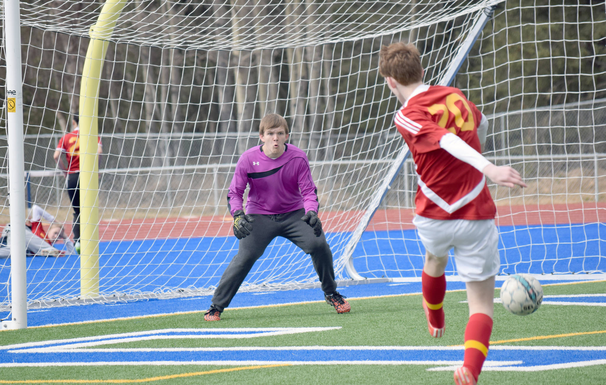 Soldotna goalie Chase Miller defends a cross in front of his goal by West Valley's Seth Thomas on Friday, April 28, 2017, at Soldotna High School. (Photo by Jeff Helminiak/Peninsula Clarion)