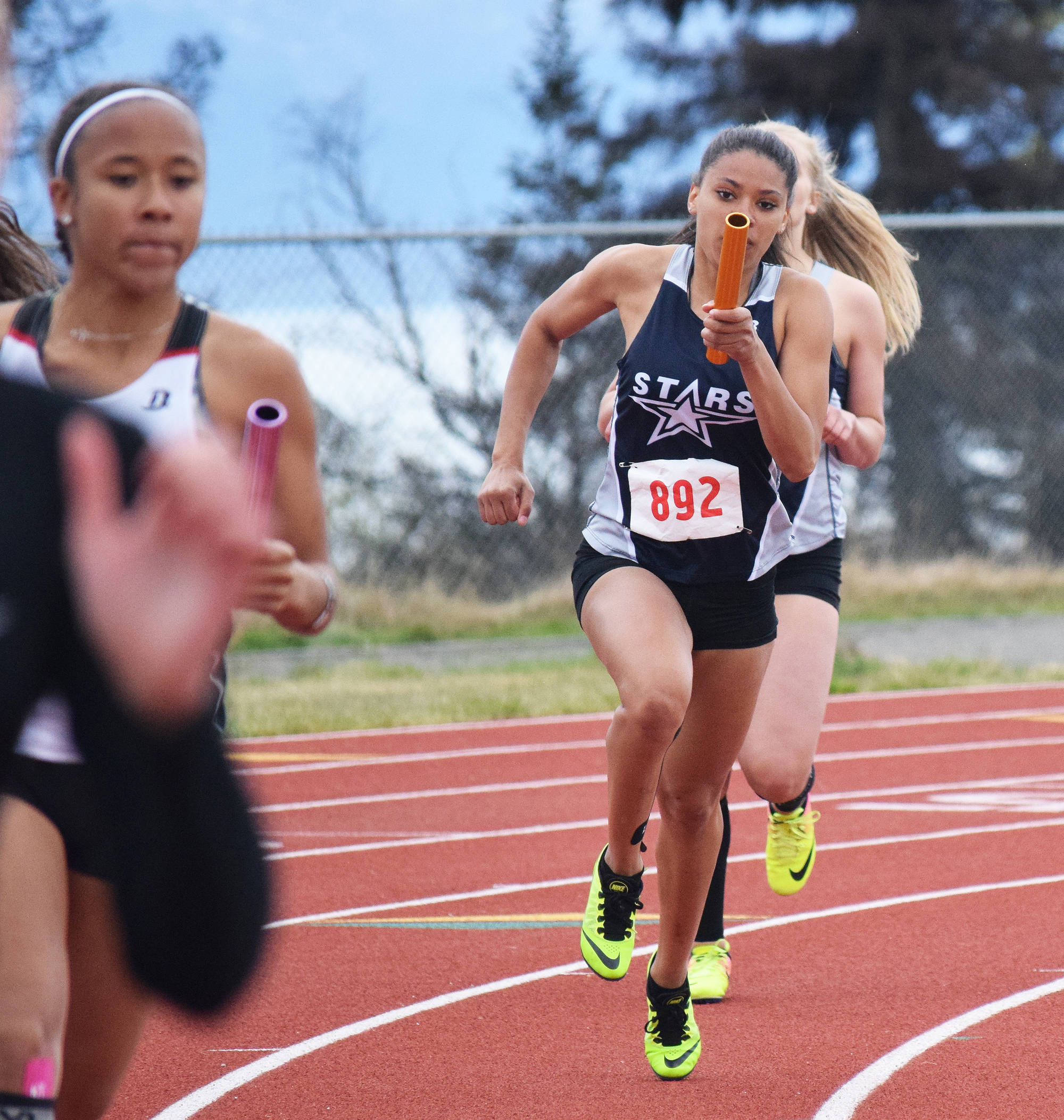 Soldotna's Brittany Taylor hands the baton off to teammate Tovia Bremond-Hilton in the Class 4A girls 800-meter relay Saturday at the Region III track & field championships in Homer. (Photo by Joey Klecka/Peninsula Clarion)