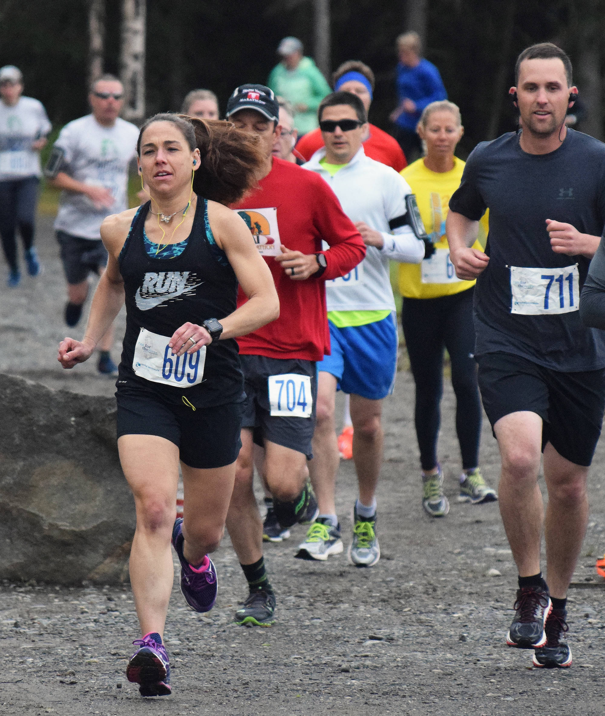 Women's Run for the River 10-mile runner-up Heather Moon (609) leads a pack of racers out onto the course Saturday morning in Soldotna, with women's 10-mile race winner Bethany Tietz (in yellow shirt) following closely. (Photo by Joey Klecka/Peninsula Clarion)