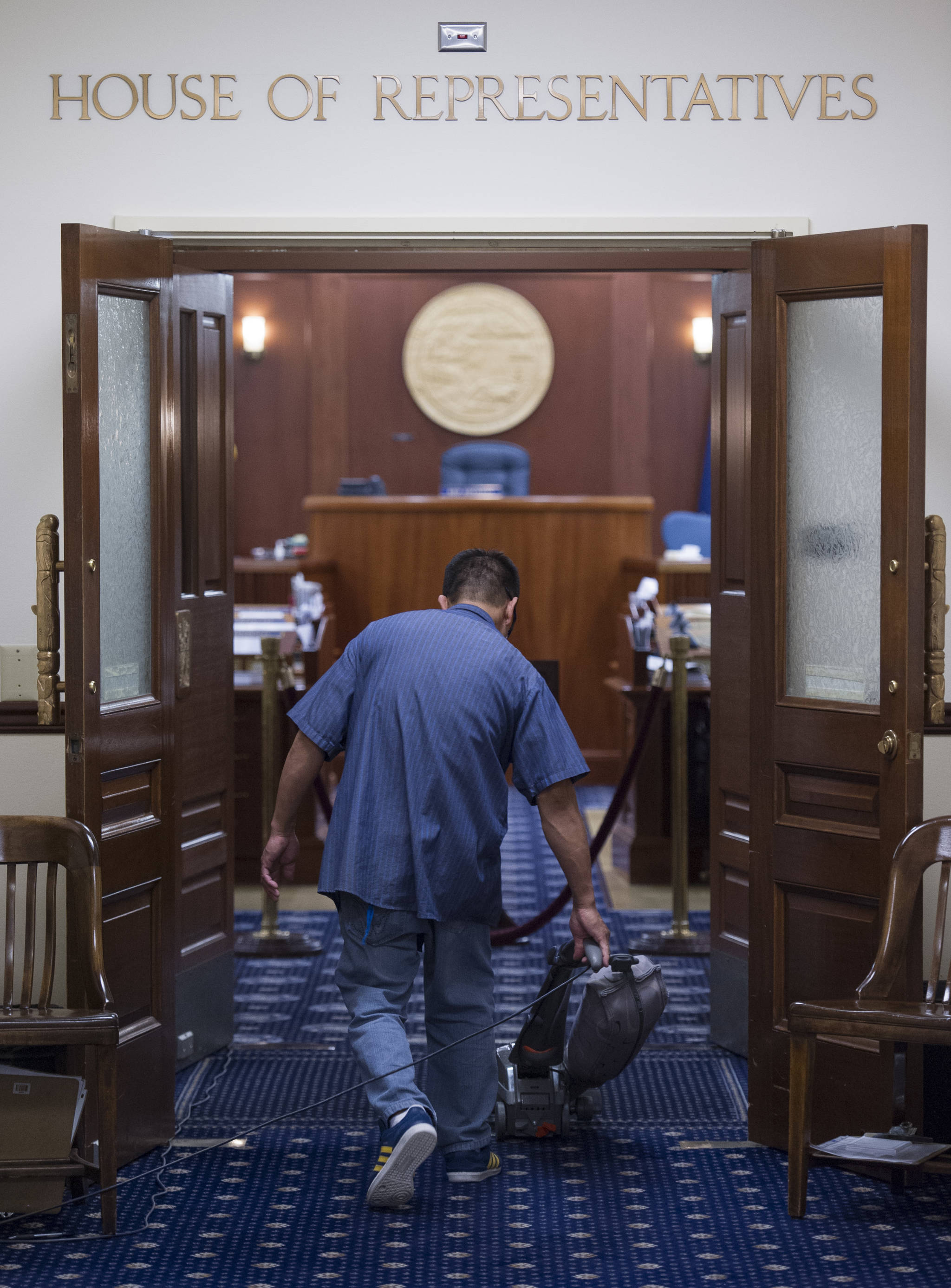 A janitor vacuums at the Capitol just before midnight Thursday, June 23, 2017, after both the House and Senate voted to approve a budget and keep the State of Alaska from shutting down on July 1. (Michael Penn | Juneau Empire)