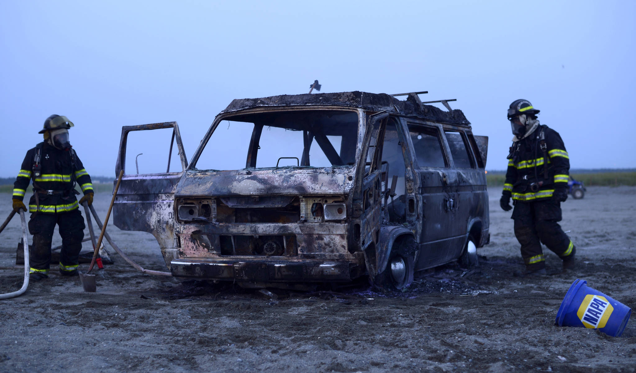 Two Kenai firefighters clean up a 1987 Volkswagen Westfallia camper van that caught fire Thursday, July 13, 2017 on the south beach in Kenai, Alaska. No one was in the van when it burnt, and there were no injuries. (Photo by Ben Boettger/Peninsula Clarion)