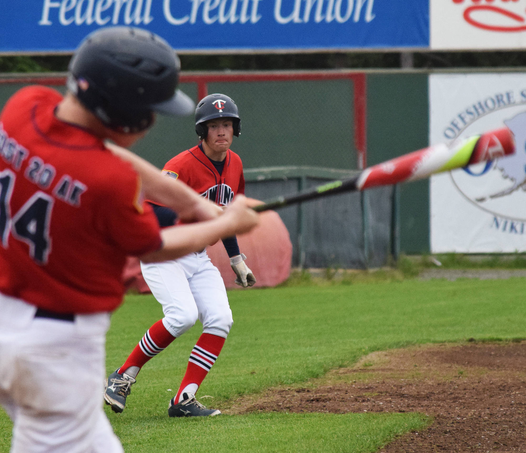Post 20 Twins' Jeremy Kupferschmid watches teammate Mose Hayes take a swing against South Post 4 Saturday at Coral Seymour Memorial Park in Kenai. (Photo by Joey Klecka/Peninsula Clarion)