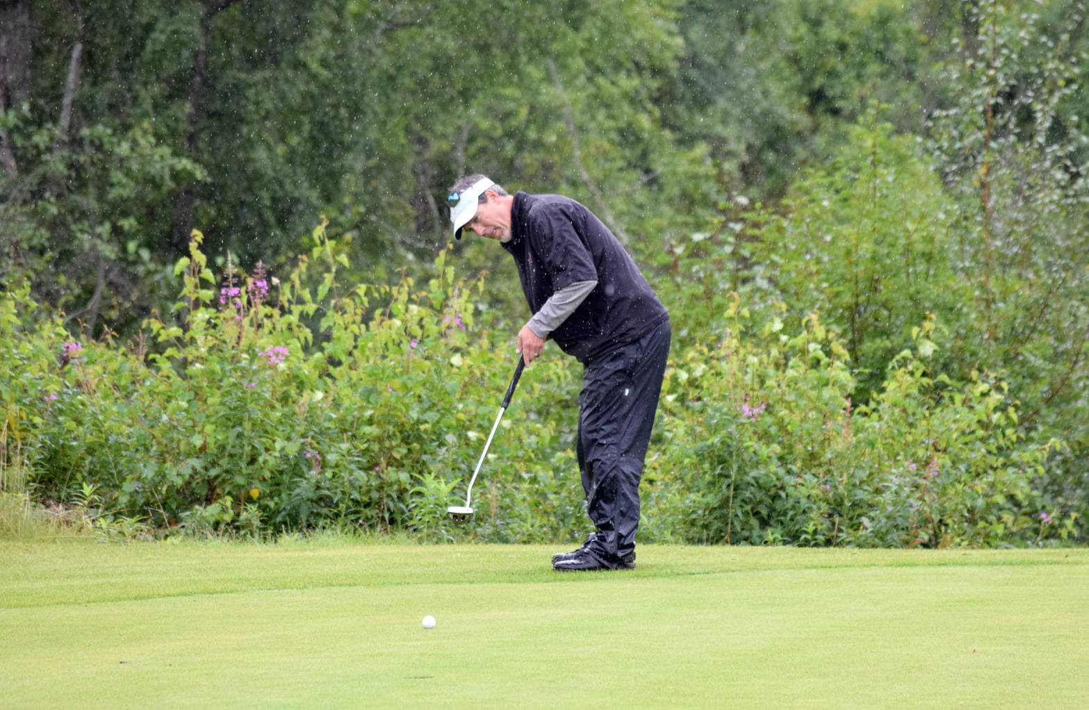 Chris Morin putts for birdie on the 18th green Sunday, Aug. 20, 2017, at the Kenai Golf Course during the Kenai Open. Morin's putt came up short and the three-time defending champ lost by one stroke to Max Dye. (Photo by Jeff Helminiak/Peninsula Clarion)