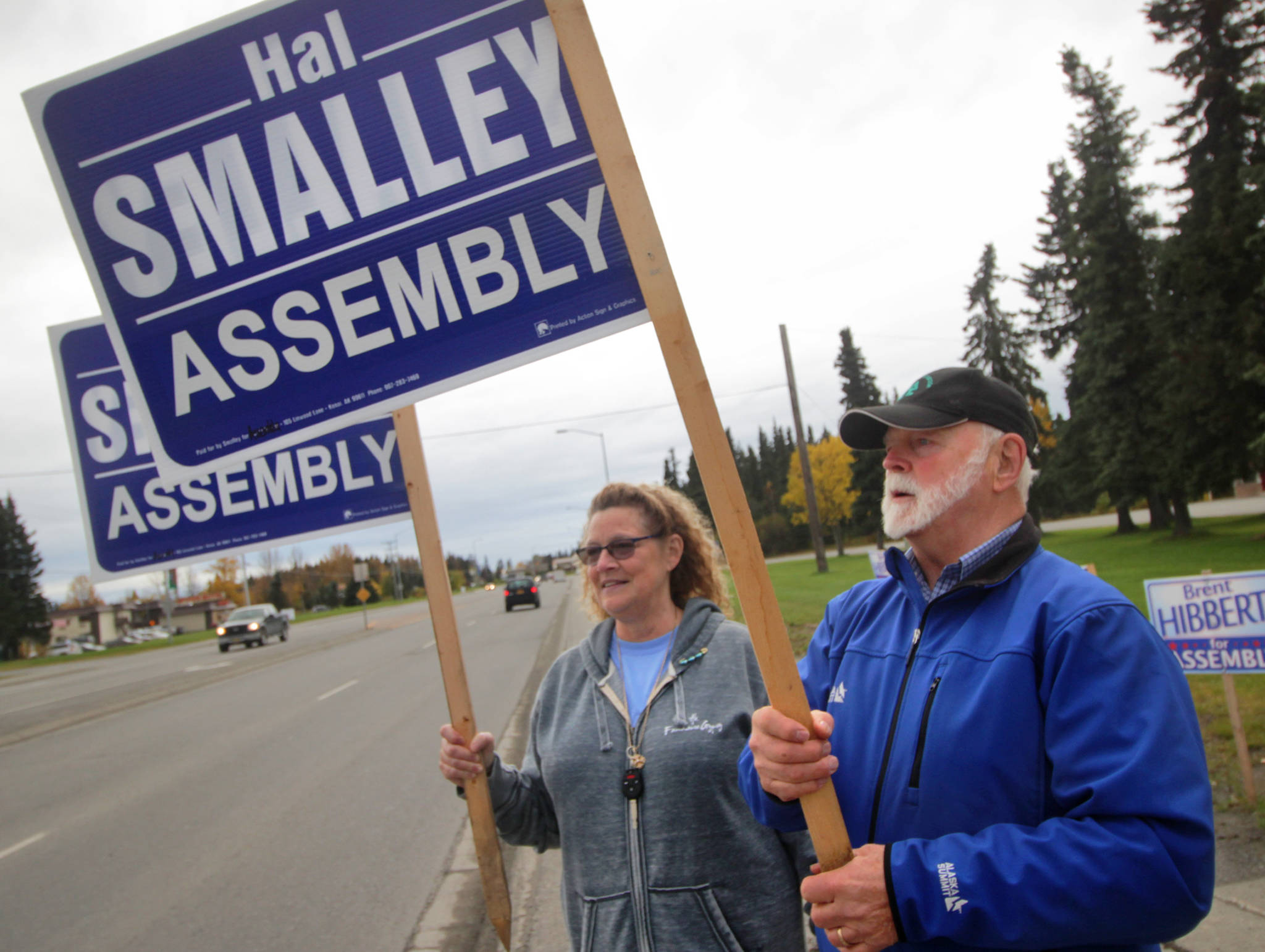 Kenai Peninsula Bourough assembly candidate Hal Smalley and supporter Michele Vasquez wave signs near the intersection of the Kenai Spur Highway and Bridge Access Road on Tuesday, Oct. 3 in Kenai. (Ben Boettger/Peninsula Clarion)