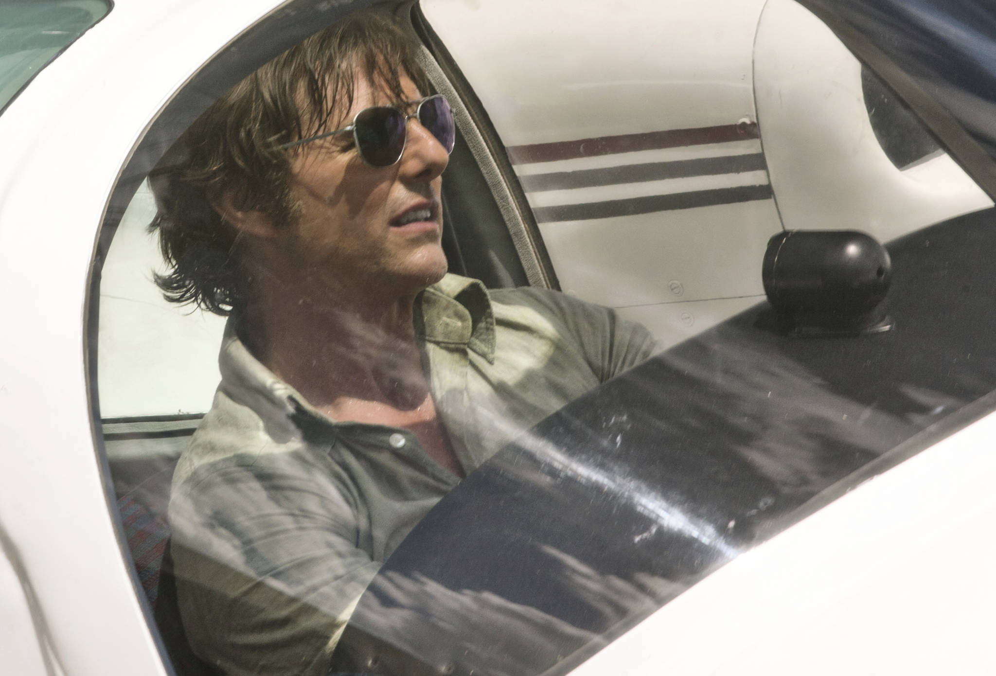 """This image released by Universal Pictures shows Tom Cruise as Barry Seal in a scene from, """"American Made."""" (David James/Universal Pictures via AP)"""