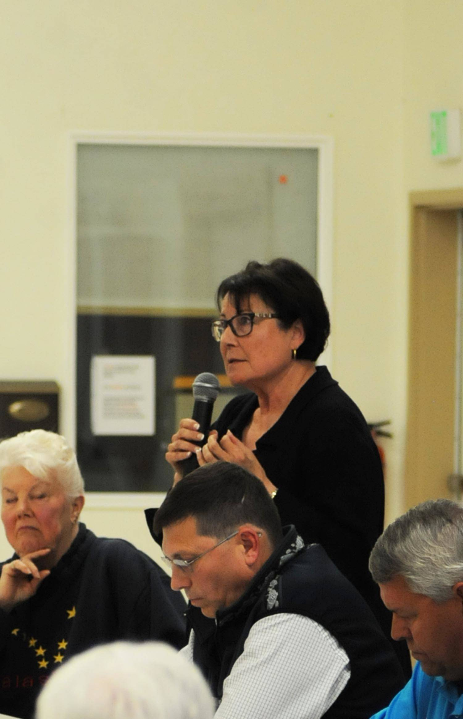 Linda Hutchings (standing), a candidate for Kenai Peninsula Borough mayor, answers a question during a forum with fellow candidates Dale Bagley (center) and Charlie Pierce (right) at the Funny River Community Center on Aug. 16, 2017 in Funny River, Alaska. (Photo by Elizabeth Earl/Peninsula Clarion, file)