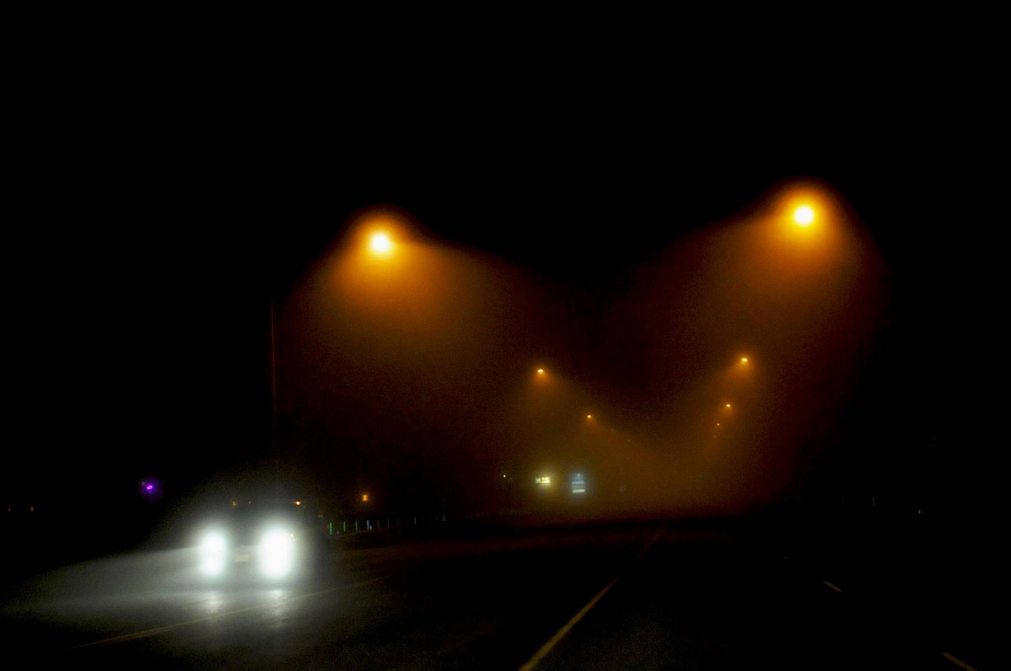 A car crosses the David E. Douthit Veterans Memorial Bridge over the Kenai River through dense fog on Tuesday, Oct. 31, 2017 in Soldotna, Alaska. A heavy fog rolled over the western Kenai Peninsula Tuesday evening, resulting in cancelled flights in and out of the Kenai Municipal Airport and ensconcing Halloween trick-or-treaters in an eerie mist colored orange or white by the streetlamps. By morning, the fog had thinned and the temperature dropped to the high 20s, with some fog predicted to continue in the morning and evening through Wednesday and Thursday, according to the National Weather Service. (Photo by Elizabeth Earl/Peninsula Clarion)