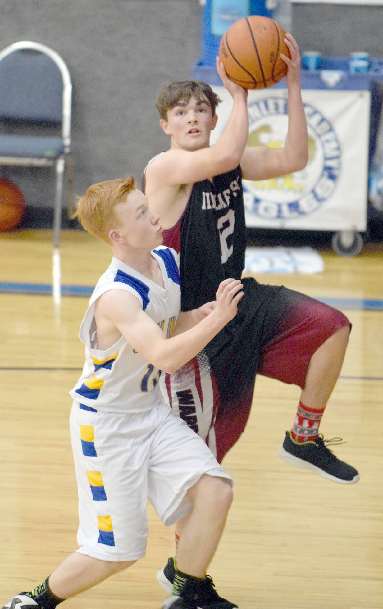 Nikolaevsk's Chris Jackson drives on Cook Inlet Academy's Lucas Cragg on Friday, Dec. 15, 2017, at Cook Inlet Academy. (Photo by Jeff Helminiak/Peninsula Clarion)