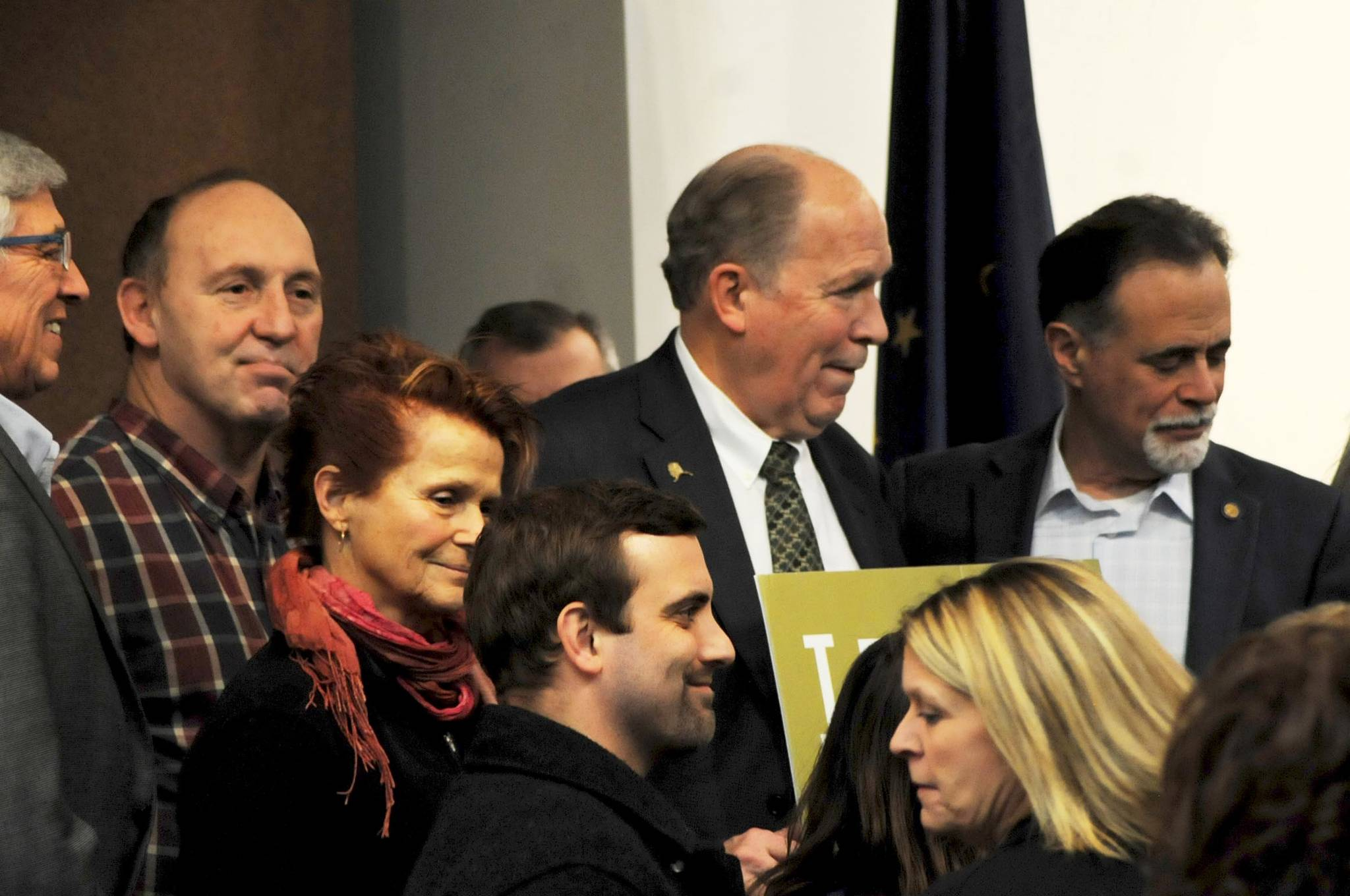 Gov. Bill Walker (center), Sen. Peter Micciche, R-Soldotna, (right) and Rep. Gary Knopp, R-Kenai, (left) stand among a group of citizens and government officials after the conclusion of a joint luncheon of the Kenai and Soldotna chambers of commerce Tuesday, Dec. 19, 2017 in Kenai, Alaska. Walker visited Kenai to address the chambers of commerce with updates on the Alaska LNG Project. (Photo by Elizabeth Earl/Peninsula Clarion)