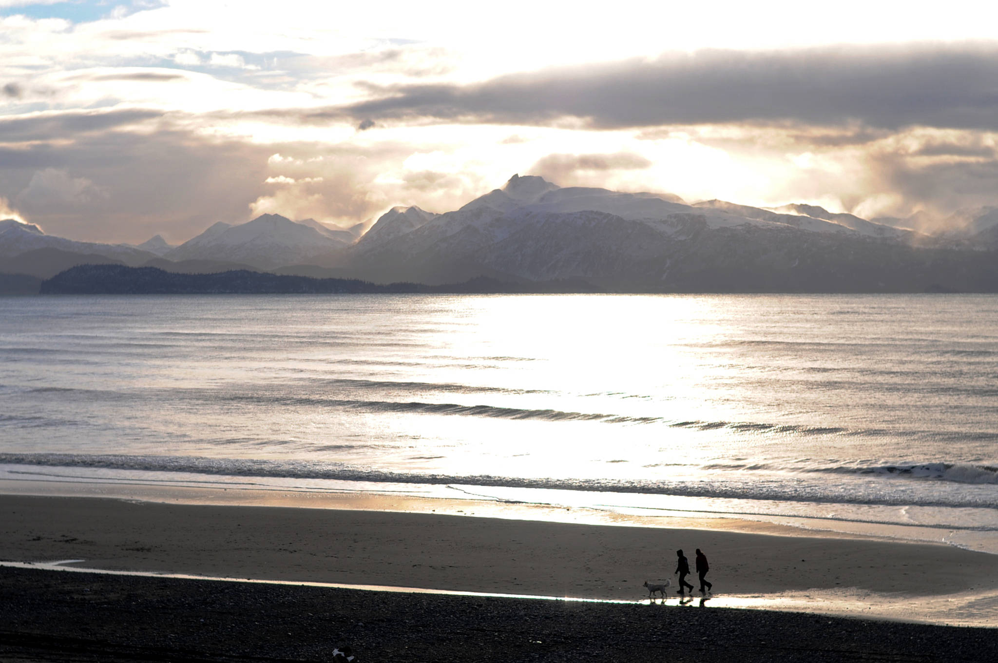 Two people walk their dog across Bishop's Beach on Dec. 3, 2016 in Homer. (Photo by Elizabeth Earl/Peninsula Clarion, file)