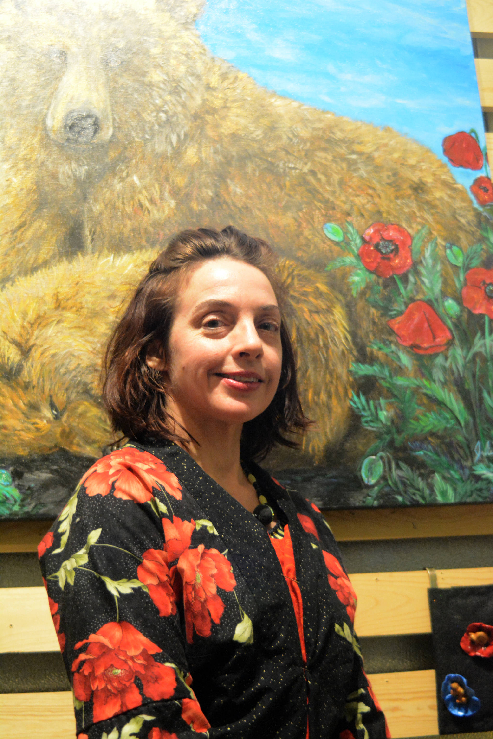 Artist Julianne Tomich stands next to one of her bear paintings at the First Friday opening of her show at Grace Ridge Brewery. (Photo by Michael Armstrong, Homer News)