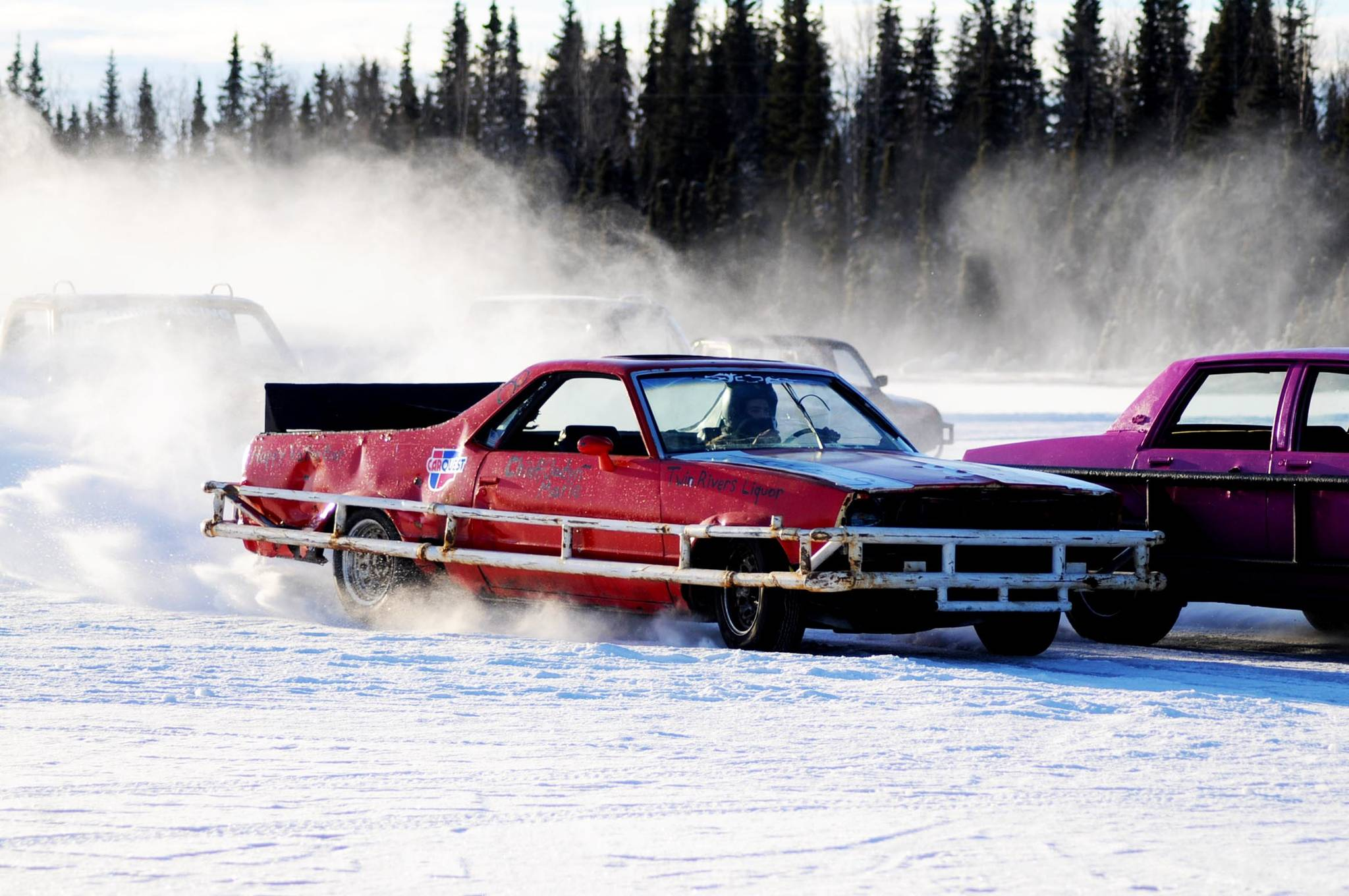 A racecar driver passes the crowd of competitors on the ice track atop a frozen lake at the Decanter Inn on Sunday, Jan. 22, 2018 in Kasilof, Alaska. Every Sunday in the winter, the Decanter Inn hosts Peninsula Ice Racing events for drivers to try their hand at the frozen track on the shallow lake at the bottom of the hill behind the inn. The racers can use studded tires on their front wheels only and equip the sides of their vehicles with bumpers as other vehicles are likely to slip and slide into them. Spinning out is common. A tow truck waits on the sidelines to retrieve drivers who get stuck on the berms alongside the track. Fans gathered Sunday despite the cold to cheer the racers on. The men race in the morning, followed by the women's races in the afternoon. (Photo by Elizabeth Earl/Peninsula Clarion)