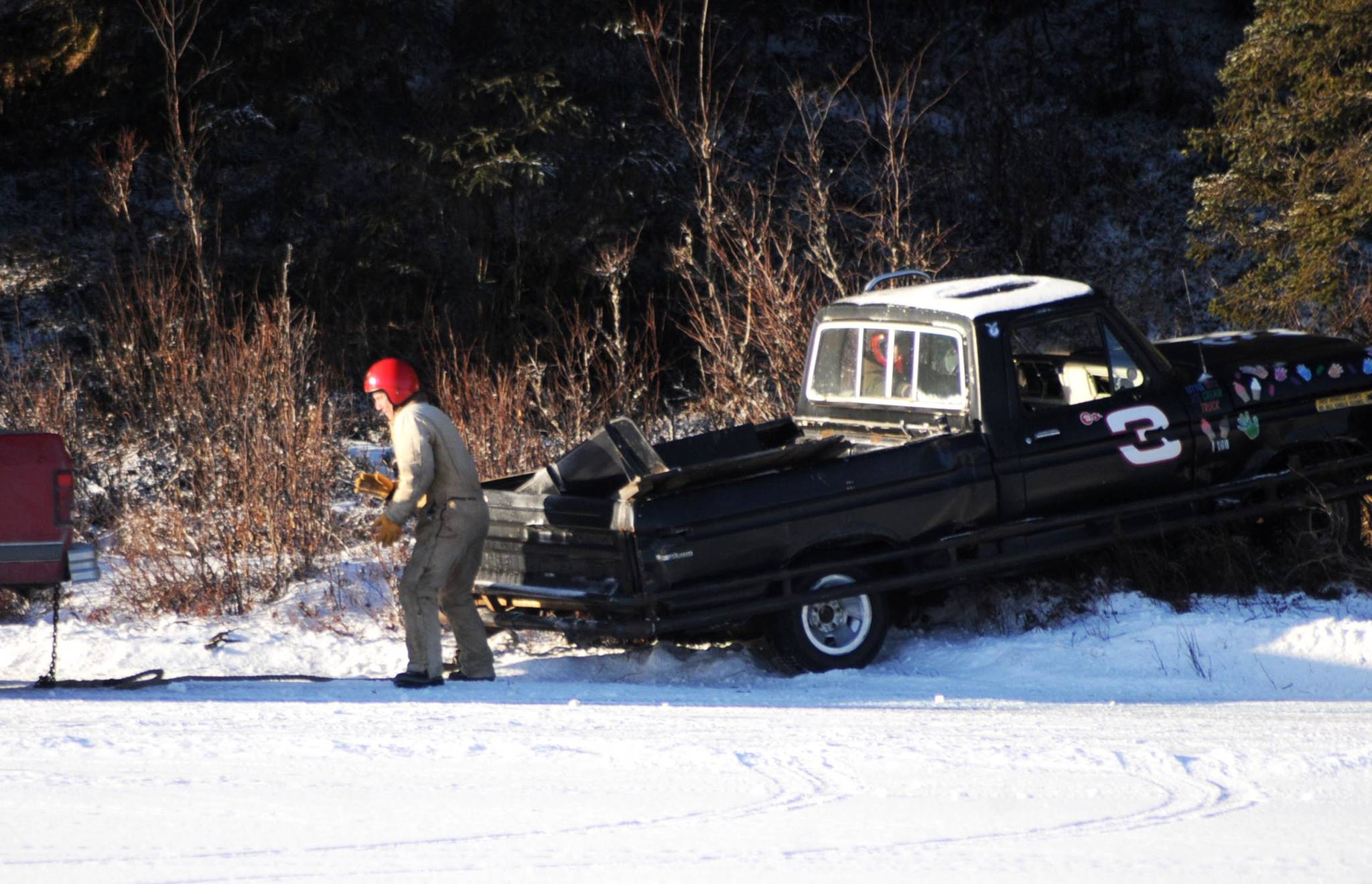 A tow truck prepares to pull a racecar driver back onto the ice track atop a frozen lake at the Decanter Inn on Sunday, Jan. 22, 2018 in Kasilof, Alaska. Every Sunday in the winter, the Decanter Inn hosts Peninsula Ice Racing events for drivers to try their hand at the frozen track on the shallow lake at the bottom of the hill behind the inn. The racers can use studded tires on their front wheels only and equip the sides of their vehicles with bumpers as other vehicles are likely to slip and slide into them. Spinning out is common. A tow truck waits on the sidelines to retrieve drivers who get stuck on the berms alongside the track. Fans gathered Sunday despite the cold to cheer the racers on. The men race in the morning, followed by the women's races in the afternoon. (Photo by Elizabeth Earl/Peninsula Clarion)