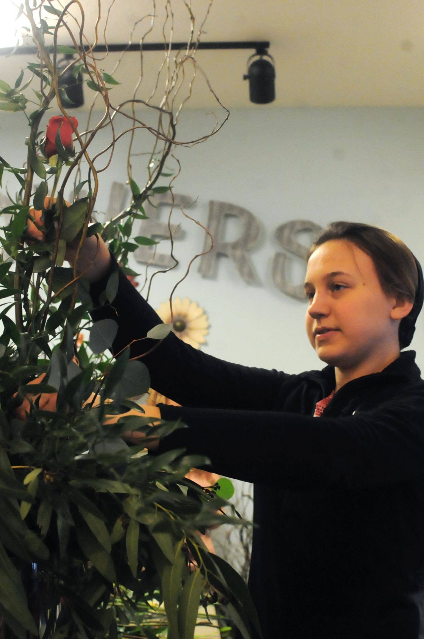 Kate's Flowers and Gifts florist Kate Mastres arranges a bouquet at the shop on Wednesday, Feb. 14, 2018 in Soldotna, Alaska. Wednesday was a busy day for the shop, with the Valentine's Day holiday. Mastres said she had been at the shop until 3:30 a.m. Wednesday morning preparing for the next day and arrived at 10 a.m. The shop does custom bouquets as well as some pre-designed ones, she said. (Photo by Elizabeth Earl/Peninsula Clarion)