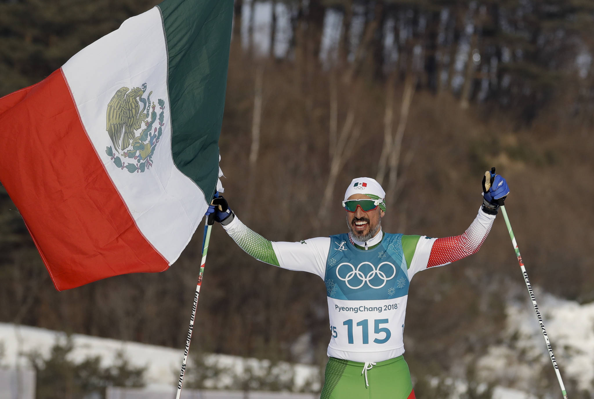 German Madrazo, of Mexico, holds up his flag after finishing last in the men's 15km freestyle cross-country skiing competition at the 2018 Winter Olympics in Pyeongchang, South Korea, Friday. (AP Photo/Kirsty Wigglesworth)