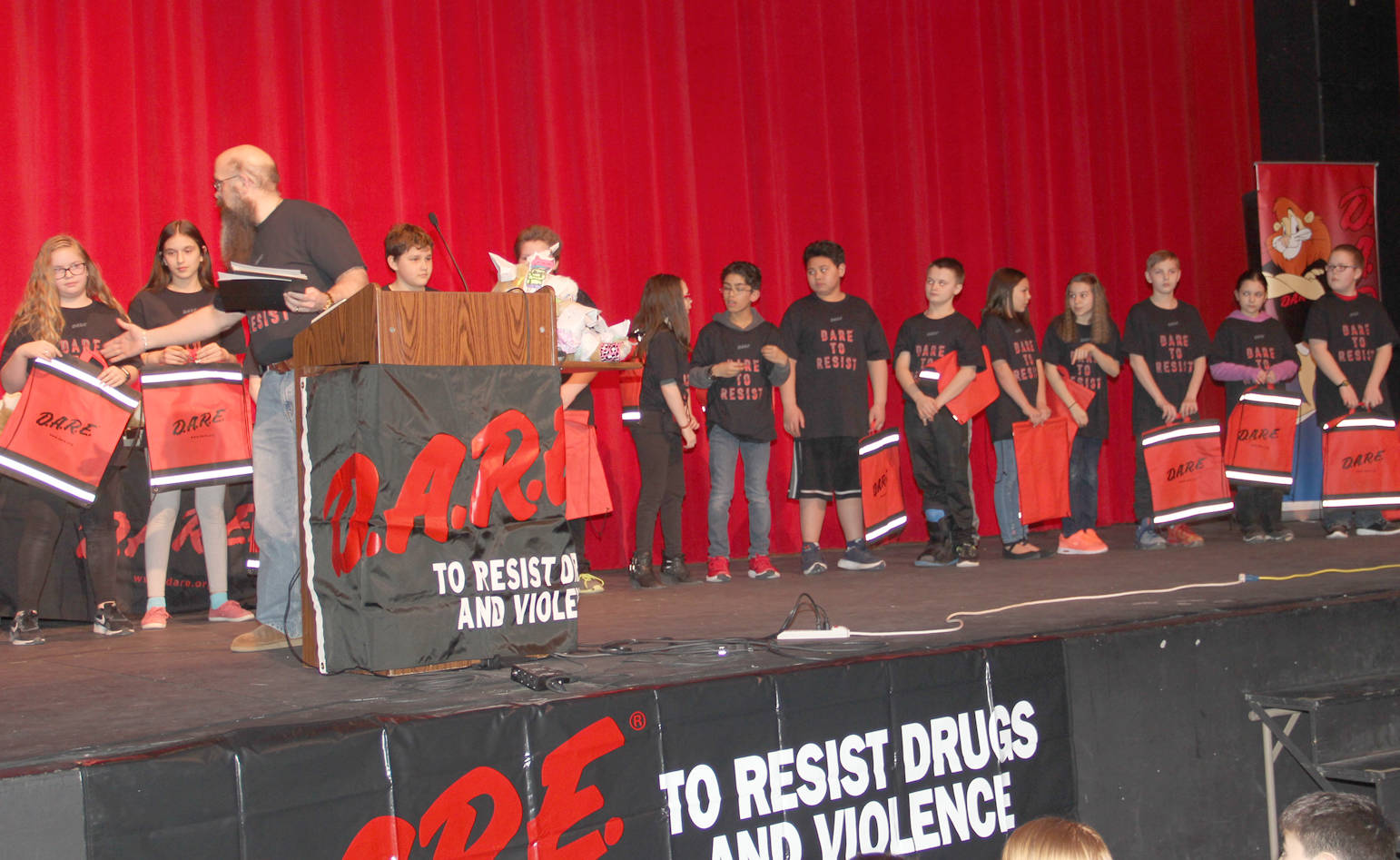 D.A.R.E. grads receive goodie bags and congratulations from community leaders.