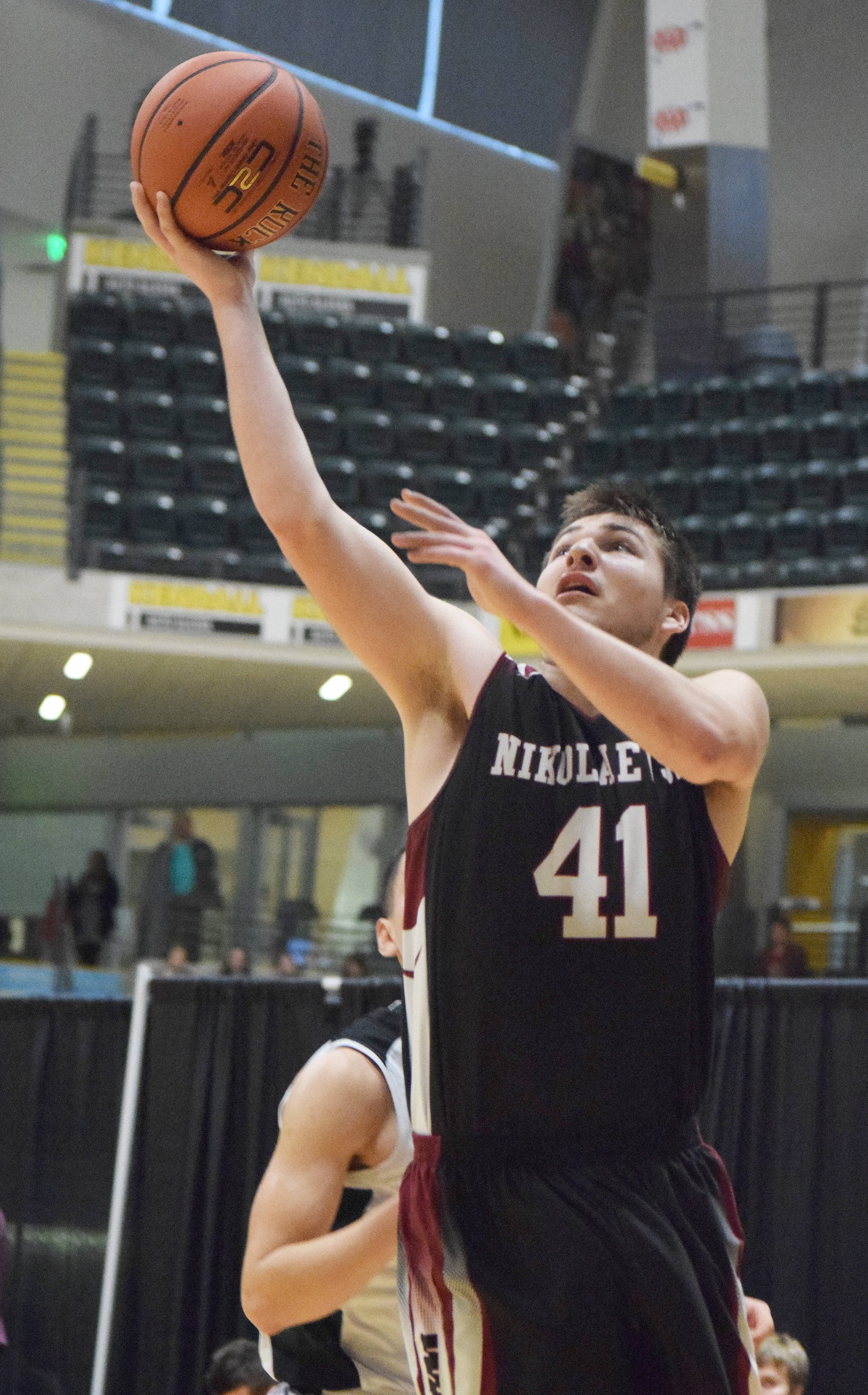 Nikolaevsk junior Michael Trail puts up a layup Friday in a Class 1A state tournament fourth-place semifinal contest against Shishmaref at the Alaska Airlines Center. (Photo by Joey Klecka/Peninsula Clarion)
