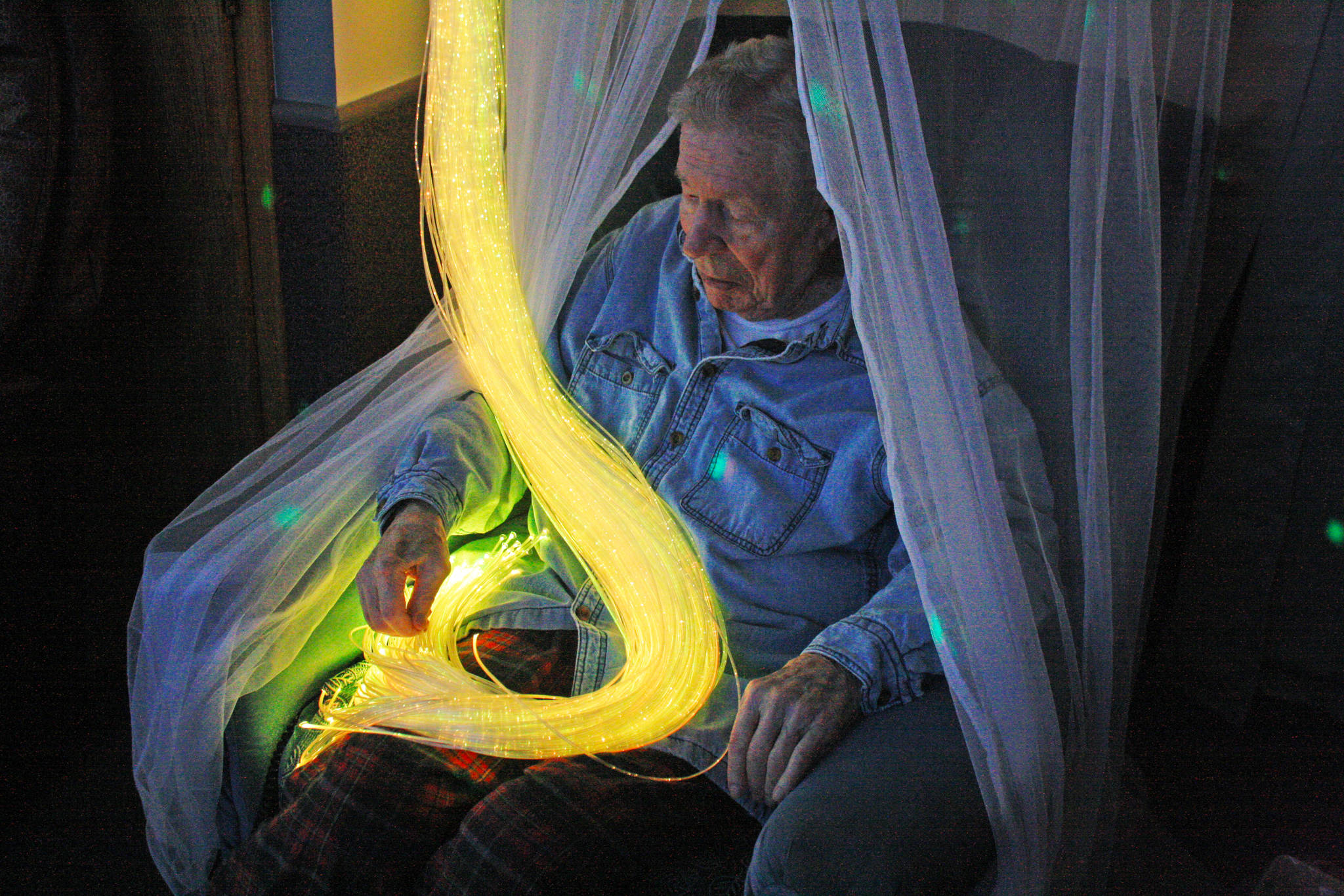 A resident at Heritage Place enjoys colored strands of light during an open house of the home's Snoezelen room on Friday, March 23 in Soldotna. (Photo by Erin Thompson/Peninsula Clarion)