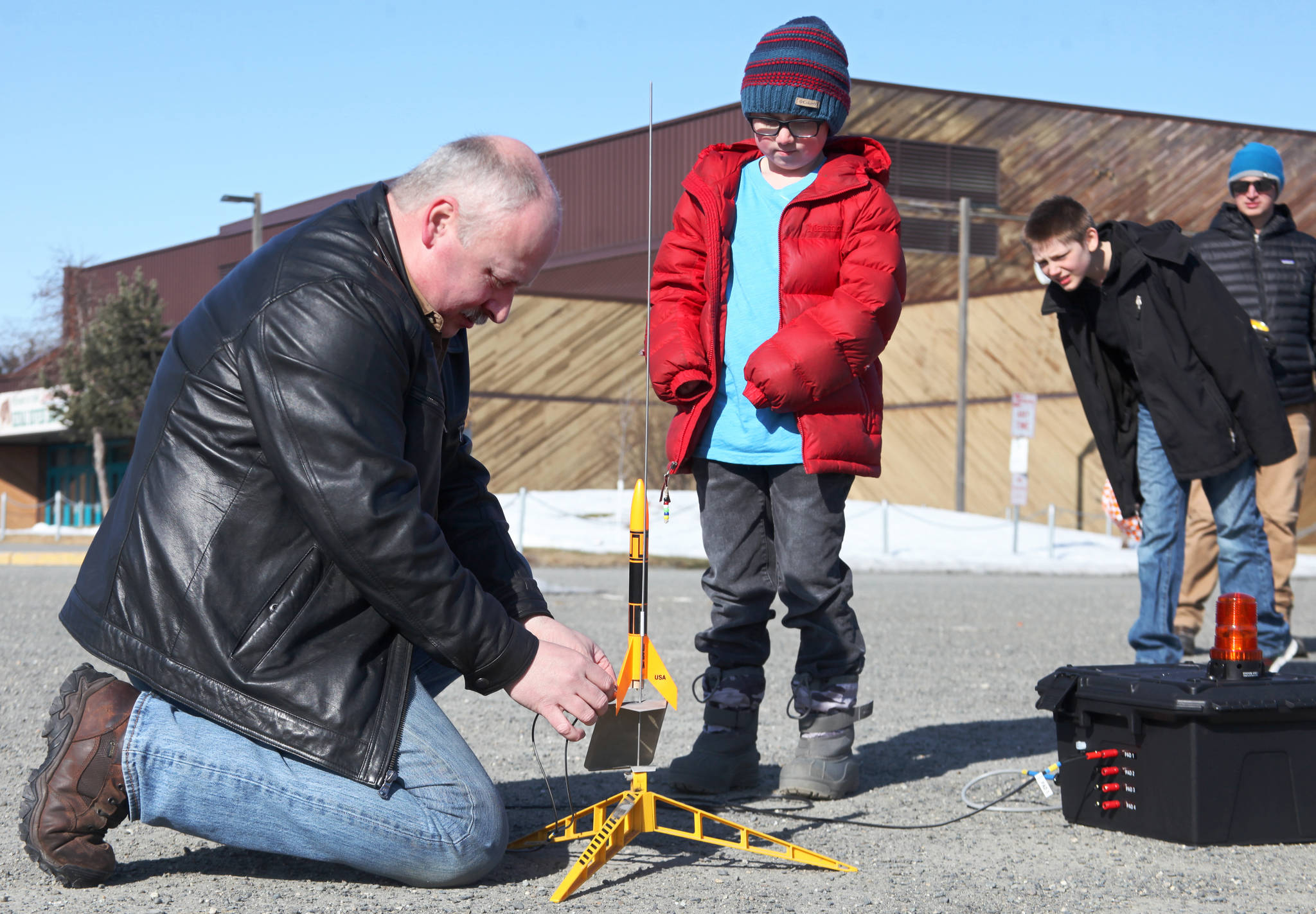 "Scott Aleckson (left) clips wires to the ignition contacts of a model rocket while students at his model rocketry session observe in the parking lot of the Soldotna Regional Sports Complex in Soldotna, Alaska on Saturday, May 31, 2018. Aleckson said he made and launched his first plastic, balsa wood, and cardboard rocket as a 4th grade student at Soldotna Elementary School. Since then he's built a custom launch system, he said, ""with recycled electronics and a lot of soldering time."" Aleckson taught Saturday's rocketry class through the Soldotna Community Schools program, and said he'd like to continue spreading the hobby. ""If I could get a model rocket club going, that'd be great,"" he said. ""Stuff like this is much more fun in a group."" (Photo by Ben Boettger/Peninsula Clarion)"