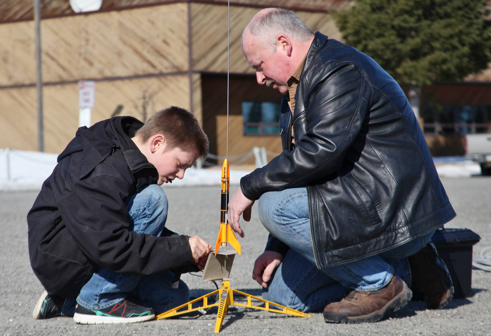 "Asa Lorentzen (left) clips wires to ignition contacts while model rocketry instructor Scott Aleckson observes in the parking lot of the Soldotna Regional Sports Complex in Soldotna on Saturday. Aleckson said he made and launched his first plastic, balsa wood, and cardboard rocket as a 4th grade student at Soldotna Elementary School. Since then he's built a custom launch system, he said, ""with recycled electronics and a lot of soldering time."" Aleckson taught Saturday's rocketry class through the Soldotna Community Schools program, and would like to continue spreading the hobby. ""If I could get a model rocket club going, that'd be great,"" he said. ""Stuff like this is much more fun in a group."" (Photo by Ben Boettger/Peninsula Clarion)"