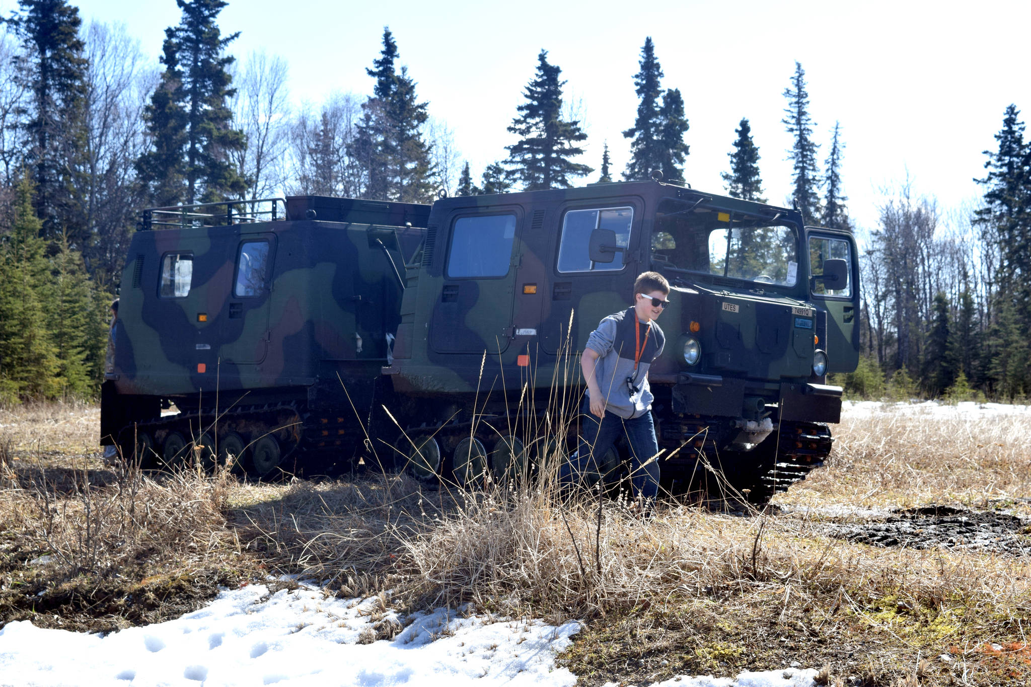 A guest at Saturday's National Guard Demo Day at the Kenai Armory in Kenai walks from a small until support vehicle, which is used by the Guard to traverse all different types of terrain. (Photo by Kat Sorensen/Peninsula Clarion)