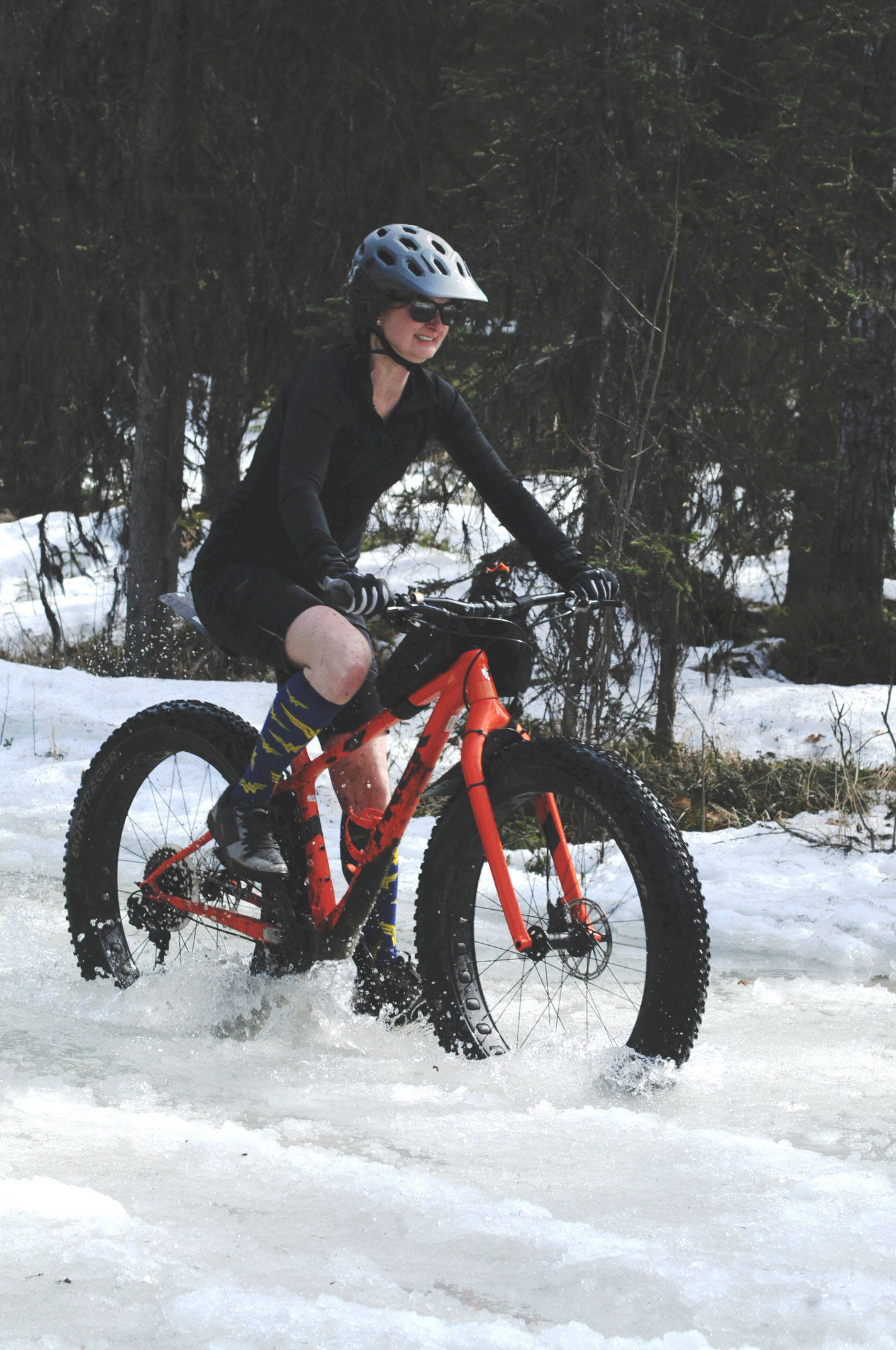 Jen Showalter of Kenai navigates her fatbike through a deep icy puddle on the Wolverine Trail during the 2018 Choose Your Weapon race at Tsalteshi Trails on Sunday, April 15, 2018 in Soldotna, Alaska. Racers completed two 5-kilometer laps around the lower trails by running, biking or skiing, with the option of switching between laps for extra points. Most of the trails had some snow with patches of wet mud sprinkled throughout as spring temperatures begin to dominate the central Kenai Peninsula. (Photo by Elizabeth Earl/Peninsula Clarion)