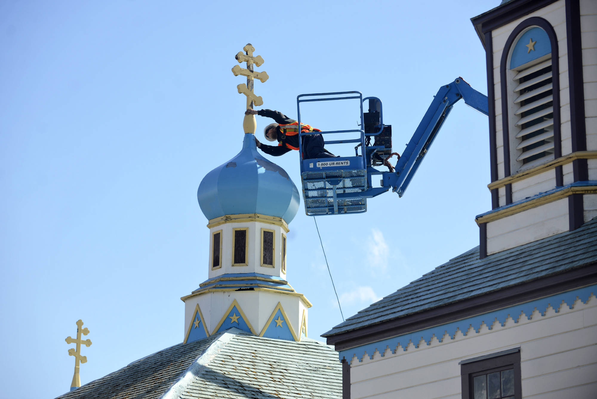 Glenn Beckmann of Rainproof Roofing inspects a weathered and tilting cross atop Kenai'sHoly Assumption of the Virgin Mary Russian Orthodox Church before removing it on Friday, May 4, 2018. Dorothy Gray , a Holy Assumption member and treasurer of the preservation nonprofit Russian Orthodox Sacred Sites in Alaska, said the church is now looking for local craftspeople interested in making replacements for the three old crosses. (Ben Boettger/Peninsula Clarion)