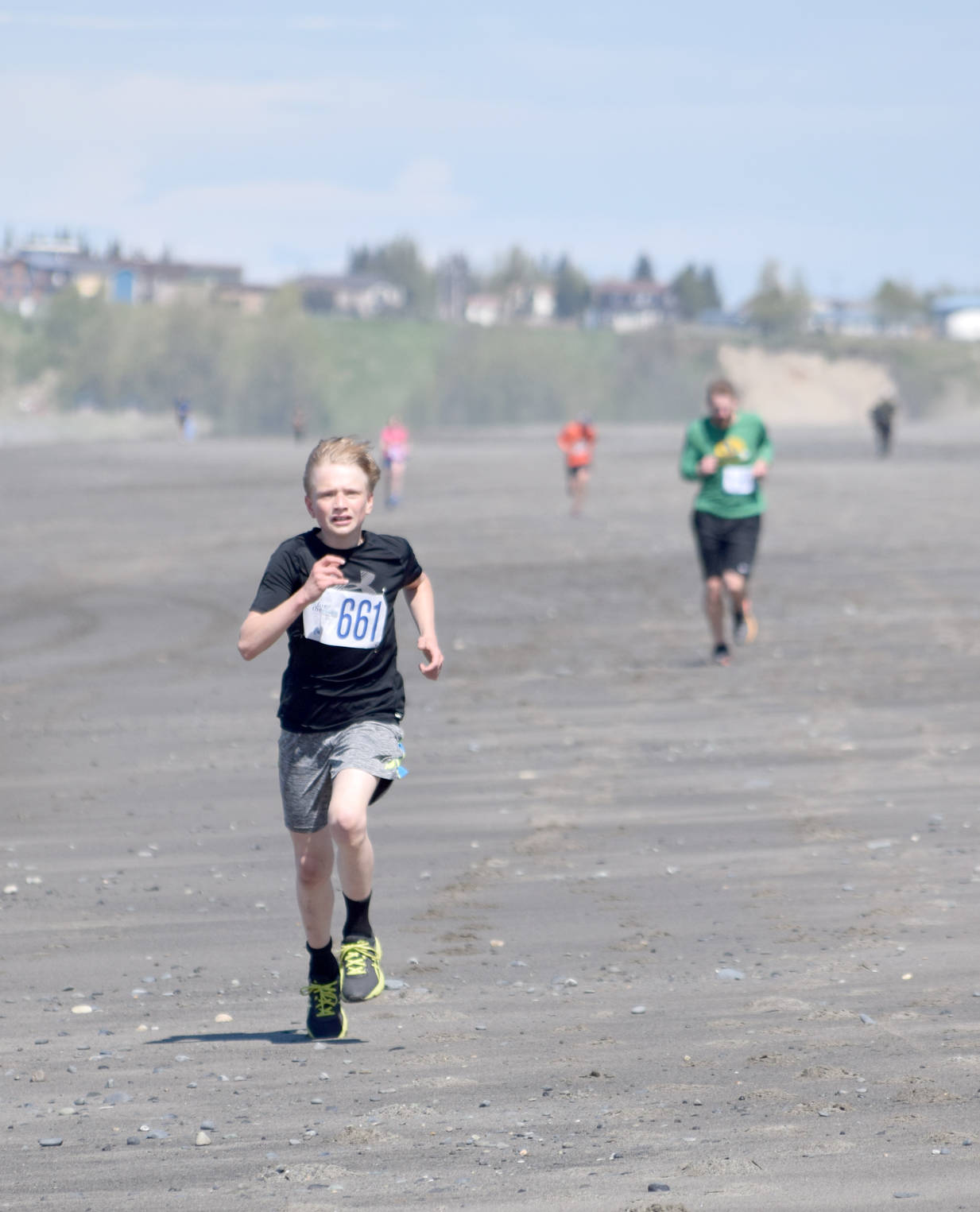 Jack Laker finishes off his victory in the three-mile run at the Mouth to Mouth Wild Run and Ride on Monday at the Kenai beach. (Photo by Jeff Helminiak/Peninsula Clarion)