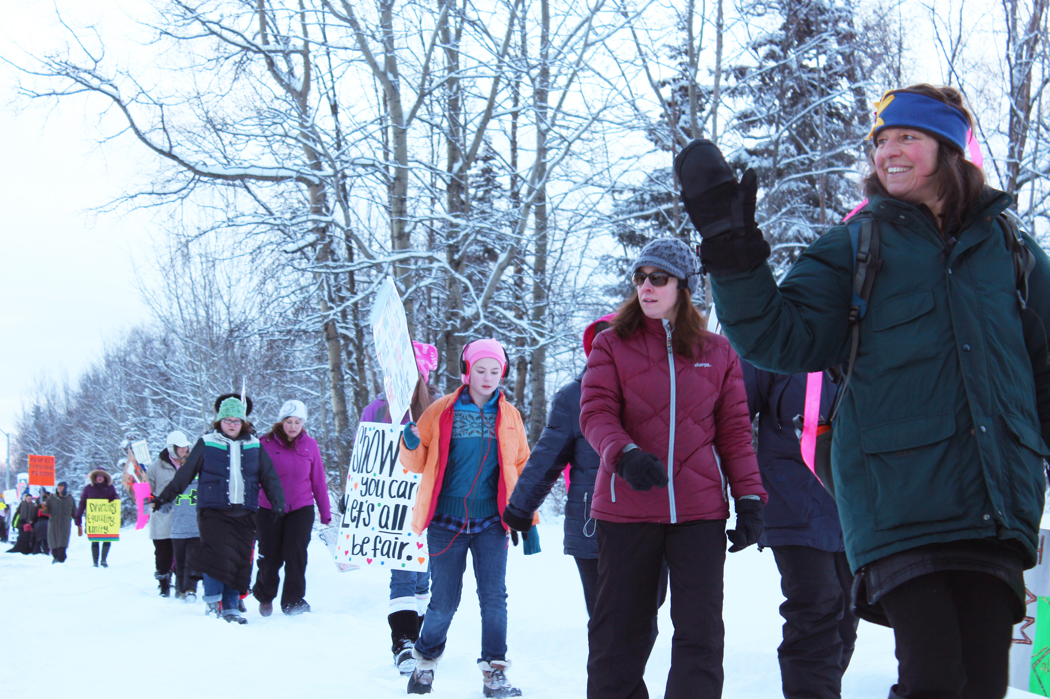 Area residents wave at cars passing by while they march down Binkley Street during a Women's March held Saturday, Jan. 21, 2017 in Soldotna, Alaska. Marchers held signs advocating for a number of issues, from women's reproductive rights to clean water. (Megan Pacer/Peninsula Clarion)