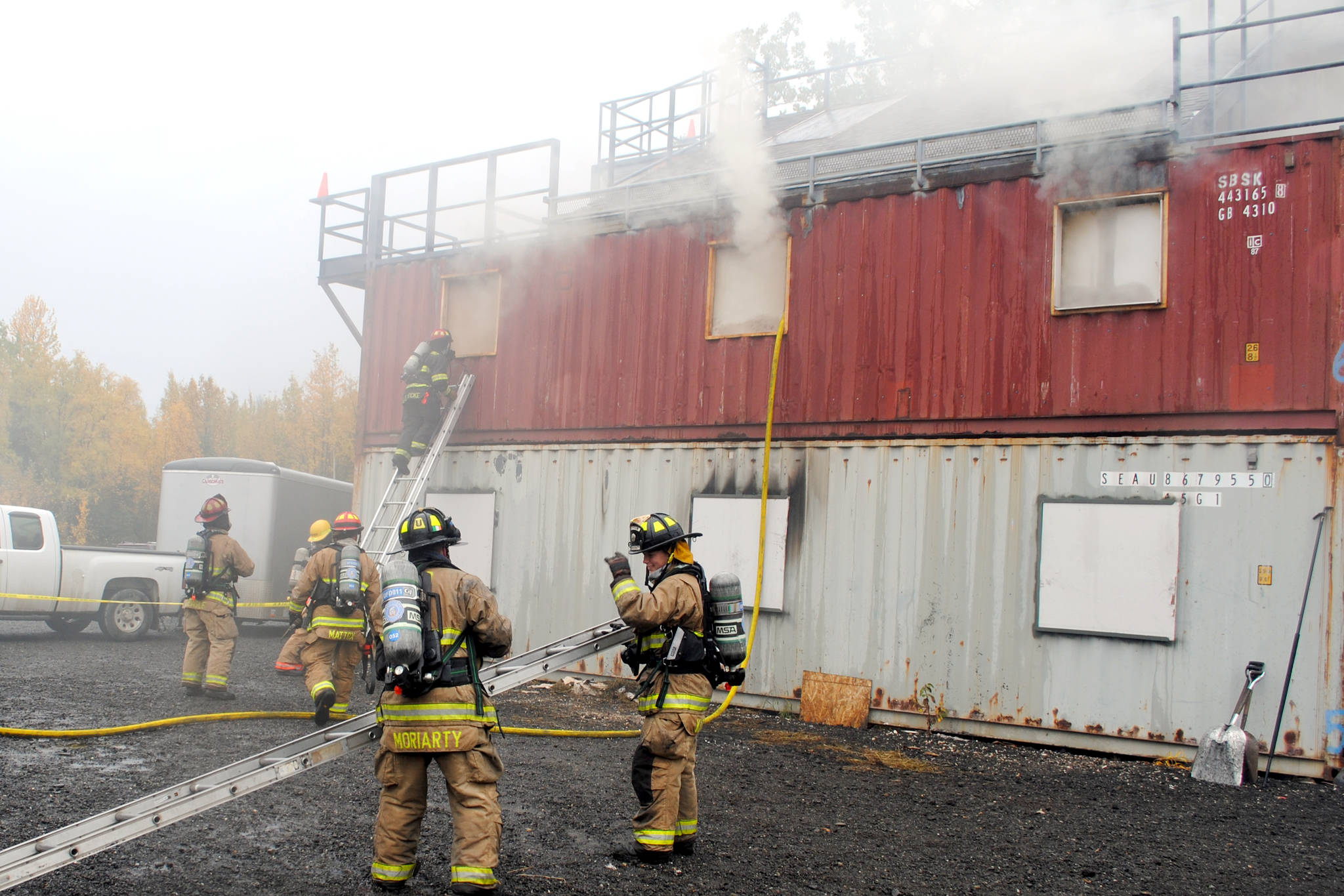 Firefighters respond to a controlled fire in a group of conexes off of Arc Loop Road in Soldotna. The area was set up to resemble a home and a fire was set in different sections of the building to test the firefighters. The training on Thursday was part of the Alaska Fire Conference which is being held in Kenai this week. (Photo by Kat Sorensen/Peninsula Clarion)
