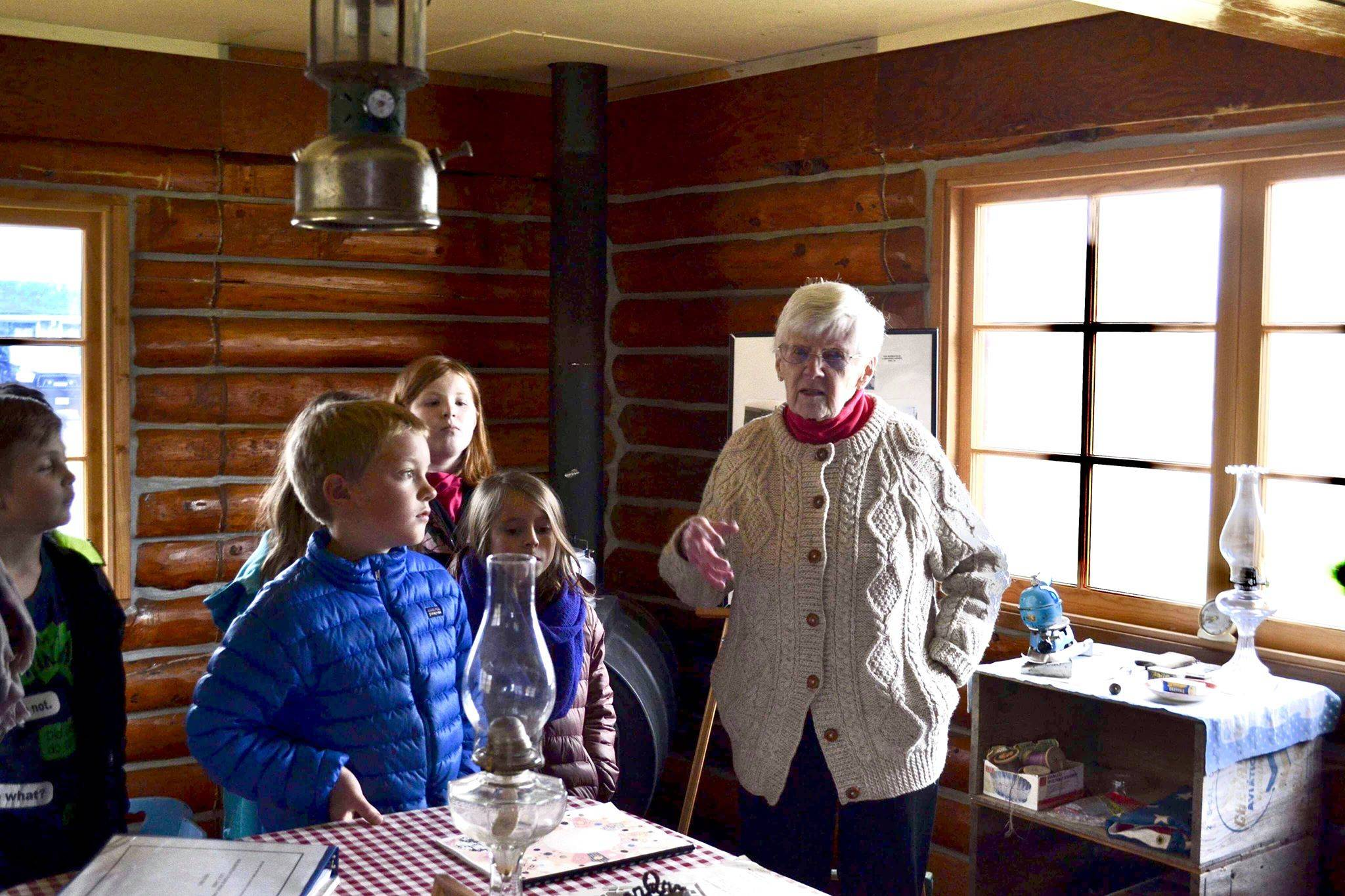 Marge Mullen shows a group of third graders around the Howard Lee Homestead, which was used as the city's first post office when she first homesteaded in Soldotna, on Wednesday, oct. 17, 2018, in Soldotna, AK. (Photo by Victoria Petersen/Peninsula Clarion)