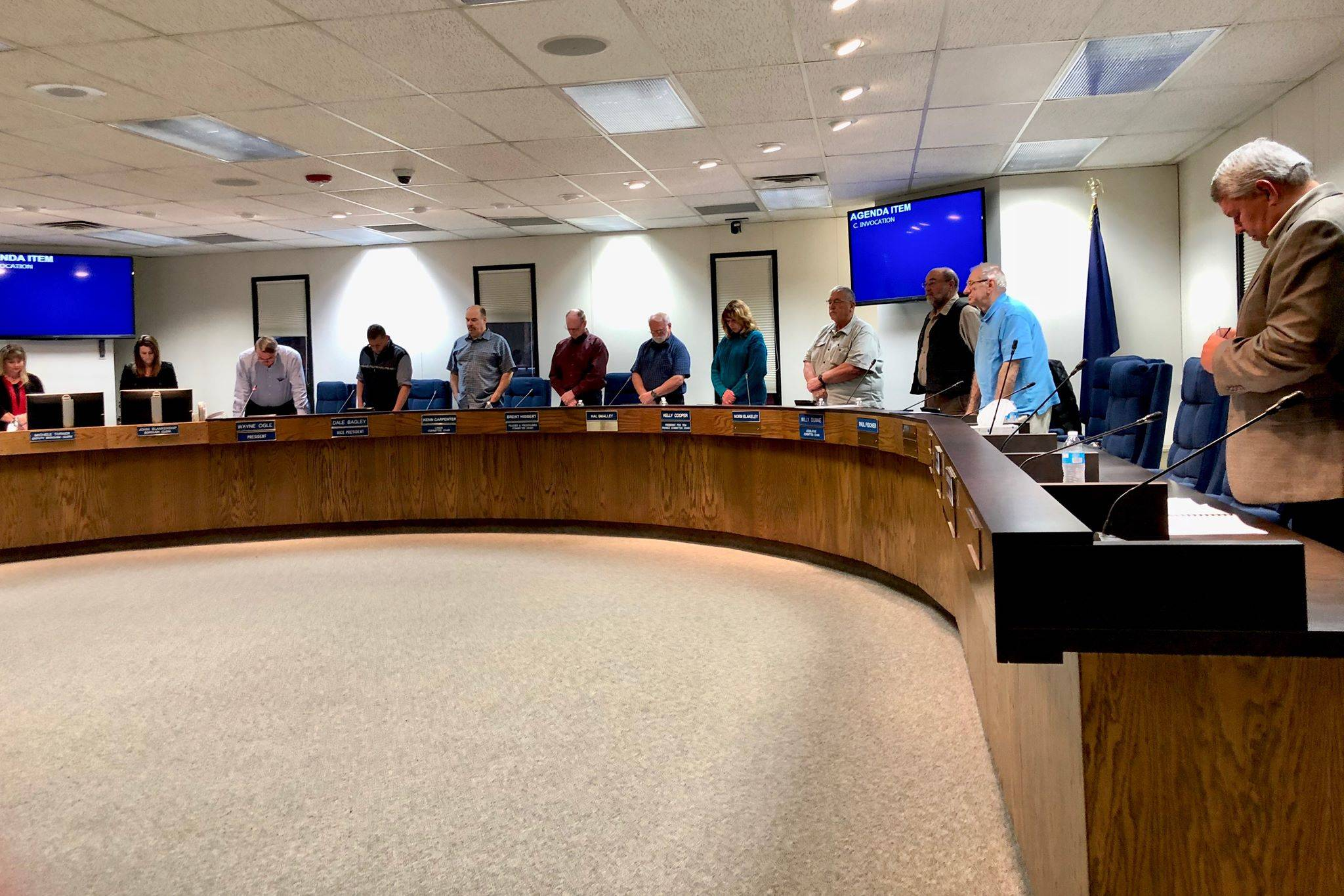 The Kenai Peninsula Borough Assembly stands in silence while Assembly President Wayne Ogle offers an invocation before the meeting, Tuesday, Oct. 23, 2018, in Soldotna, AK. (Photo by Victoria Petersen/Peninsula Clarion)