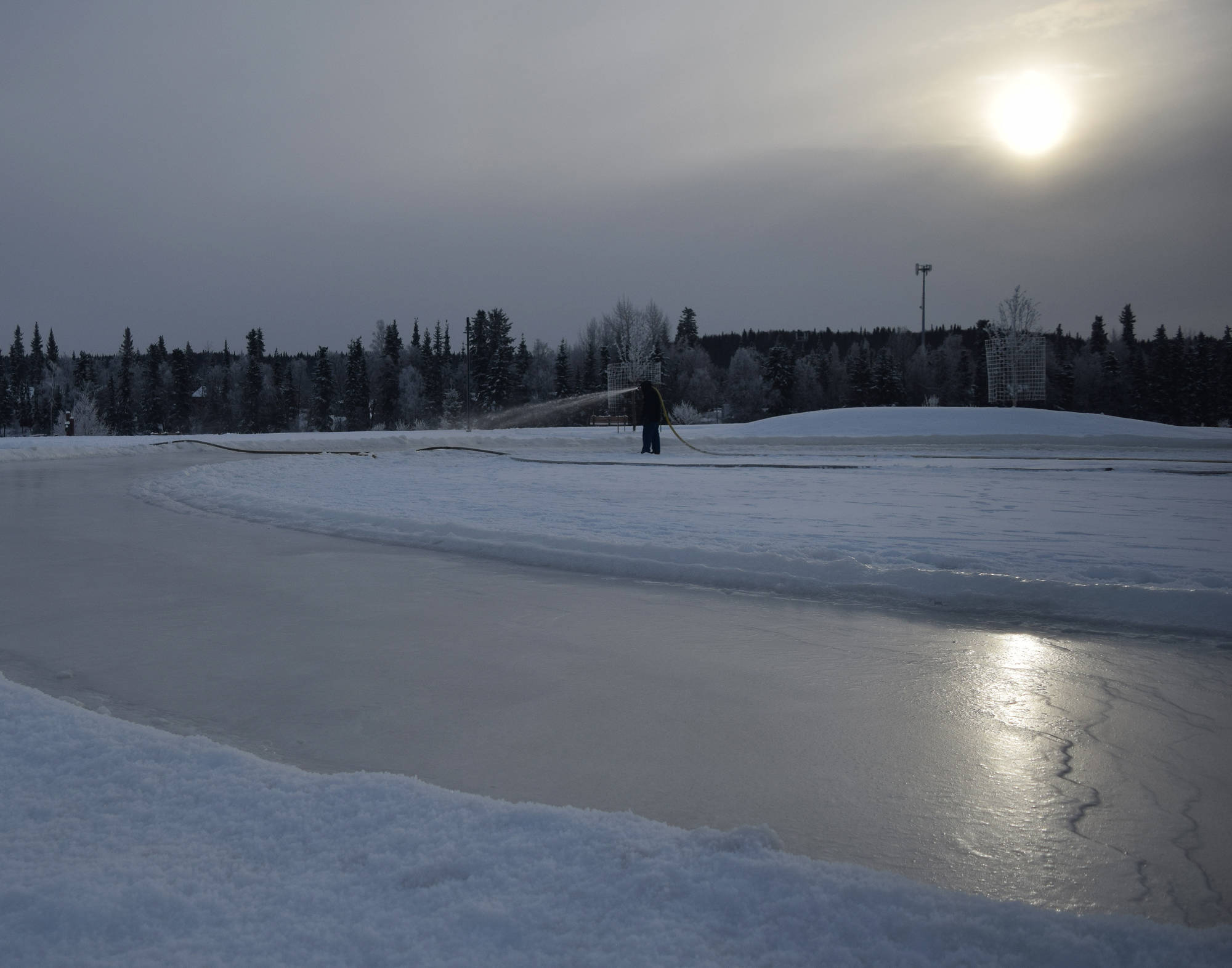 A Soldotna Parks & Recreation worker sprays a layer of water to be frozen into a skating rink Thursday at Soldotna Creek Park. (Photo by Joey Klecka/Peninsula Clarion)