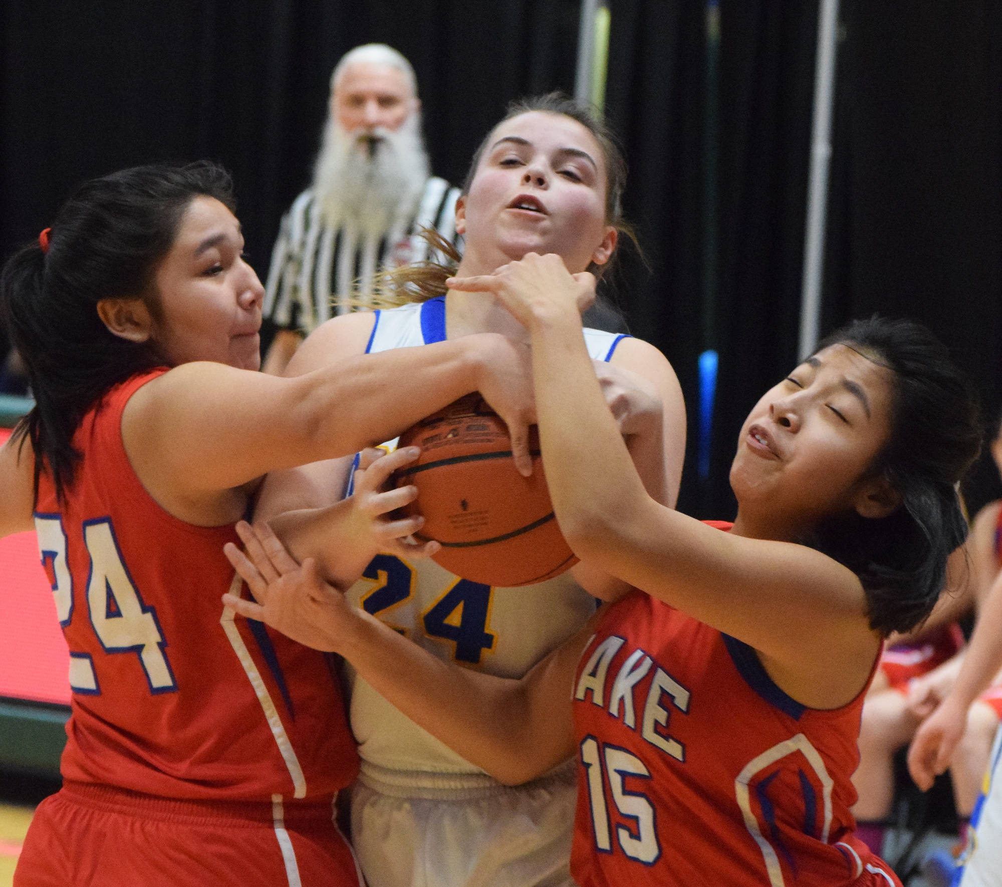 Cook Inlet Academy's Anna Cizek (middle) fights for a rebound with Kake's Felicia Ross-Shaquanie (left) and Dionna Jackson, Wednesday at the Class 1A girls basketball state tournament at the Alaska Airlines Center in Anchorage. (Photo by Joey Klecka/Peninsula Clarion)