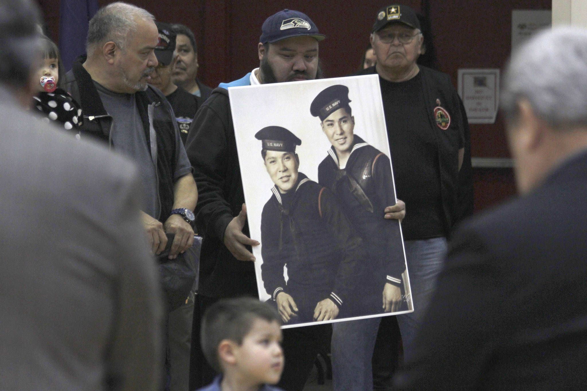 Family members of Mark and Harvey Jacobs hold a picture of the brothers during a ceremony honoring Tlingit code talkers on Monday, March 18, 2019. (Alex McCarthy | Juneau Empire)