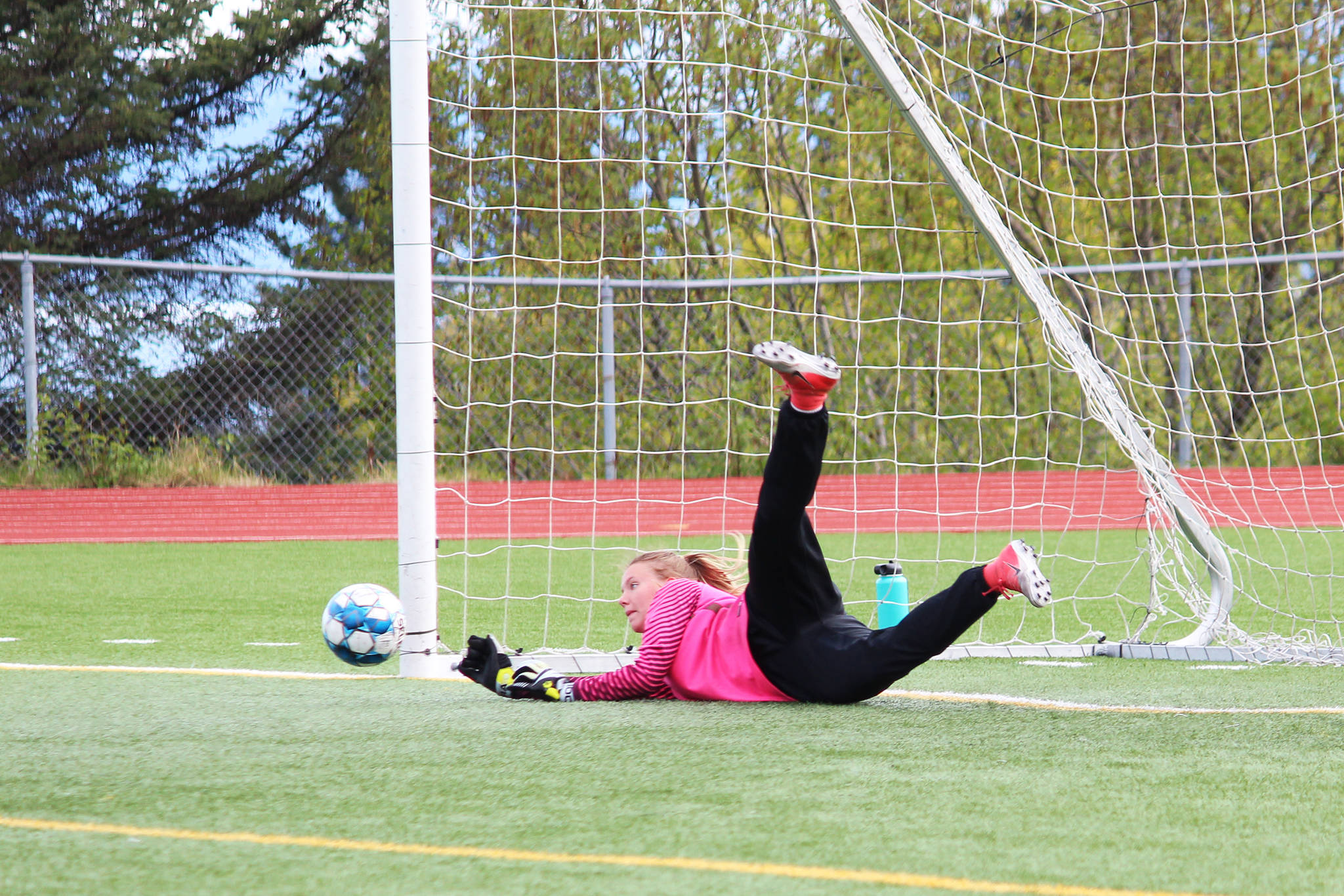 Kenai goalkeeper Kailey Hamilton dives for a ball on a penalty kick during the semi-final game of the Peninsula Conference Soccer Tournament on Friday, May 17, 2019 at Homer High School in Homer, Alaska. The game went into penalty kicks when the score remained tied after a regulation game and two halves of overtime. (Photo by Megan Pacer/Homer News)