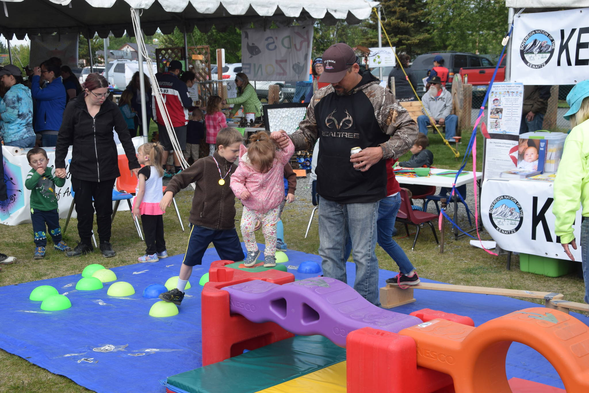Kids and parents navigate a salmon obstacle course set up by the Kenaitze Early Childhood Center during the Kenai River Festival at Soldotna Creek Park in Soldotna, Alaska on June 8, 2019. (Photo by Brian Mazurek/Peninsula Clarion)