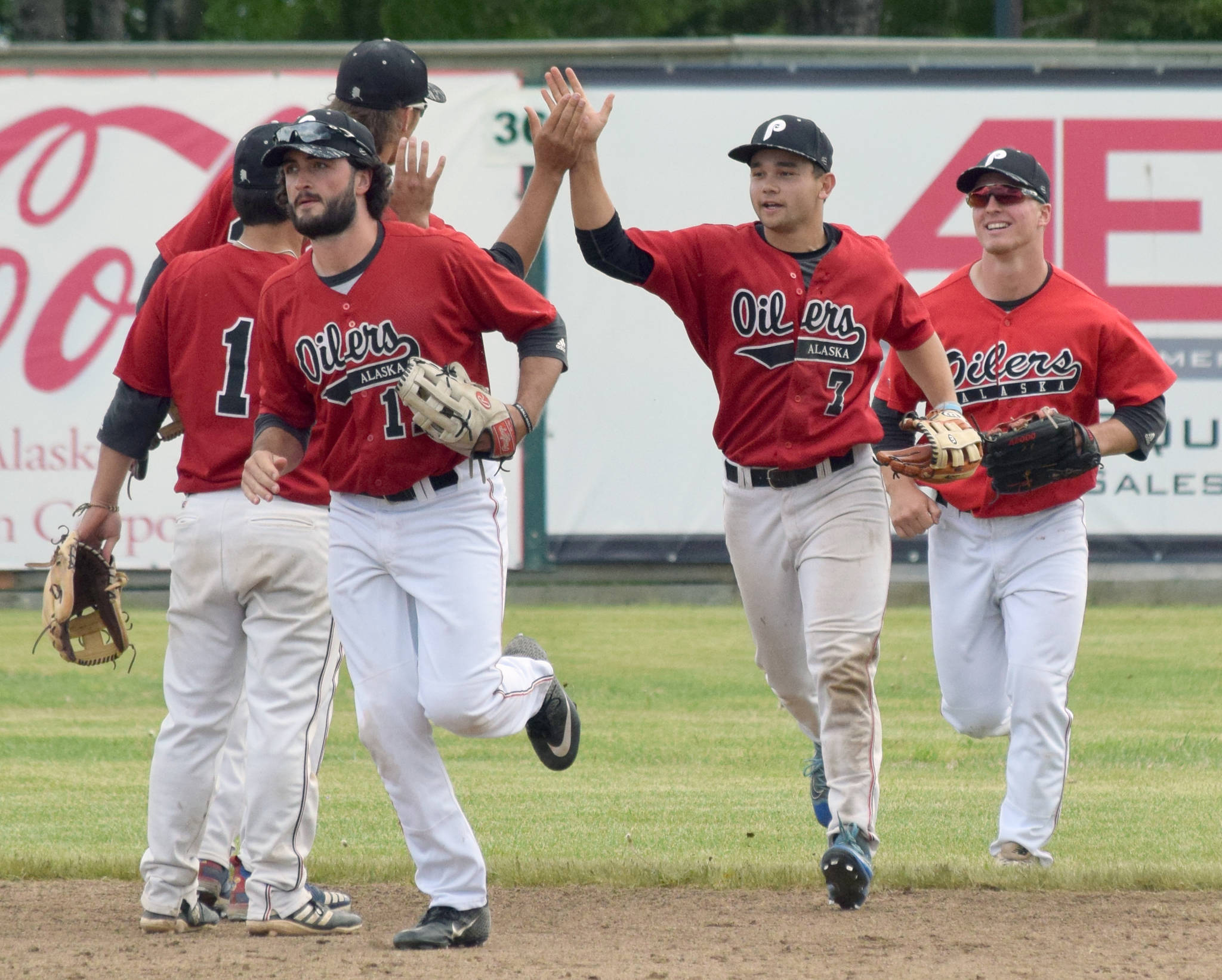 Oilers outfielders Calvin Farris, Camden Vasquez and Paul Steffensen receive congratulations after the Oilers defeated the Chugiak-Eagle River Chinooks on Sunday, June 16, 2019, at Coral Seymour Memorial Park in Kenai, Alaska.