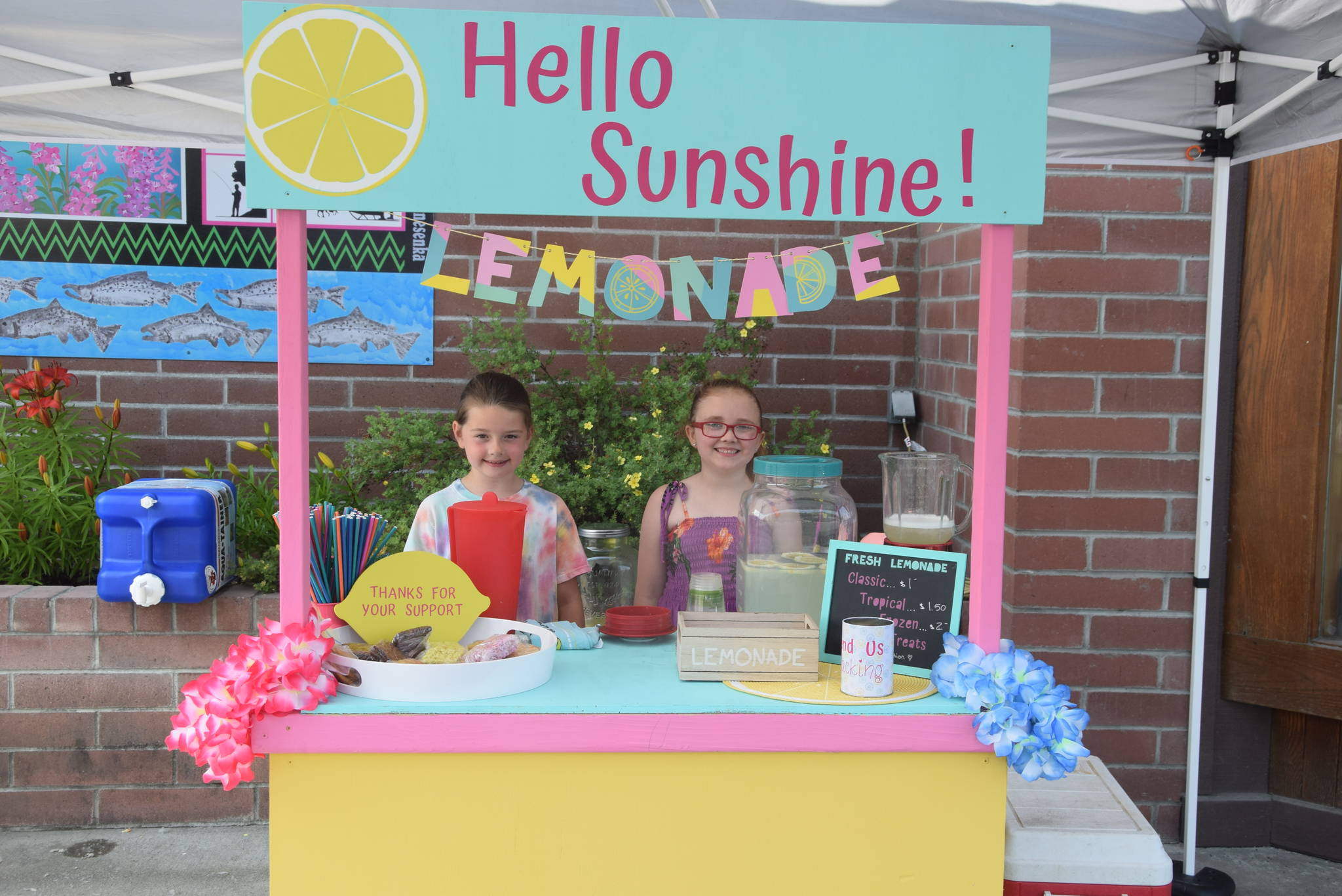 Brooklynne Timm, left, and Kinley Clack, right, smile for the camera at their lemonade stand outside of Sweeney's during Lemonade Day in Soldotna, Alaska on June 29, 2019. (Photo by Brian Mazurek/Peninsula Clarion)