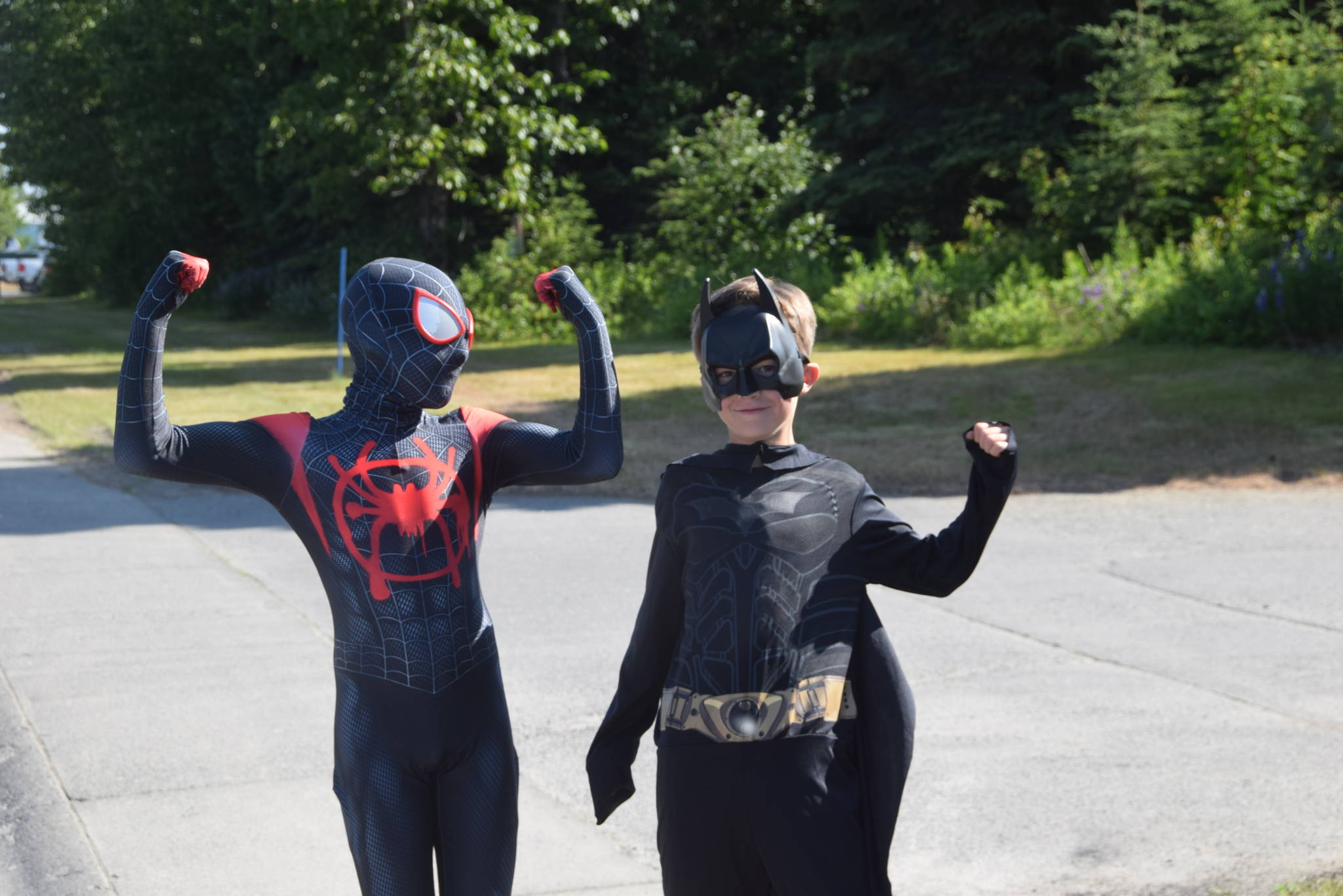 Spiderman and Batman flex their muscles during the July 4th parade in Kenai, Alaska. (Photo by Brian Mazurek/Peninsula Clarion)