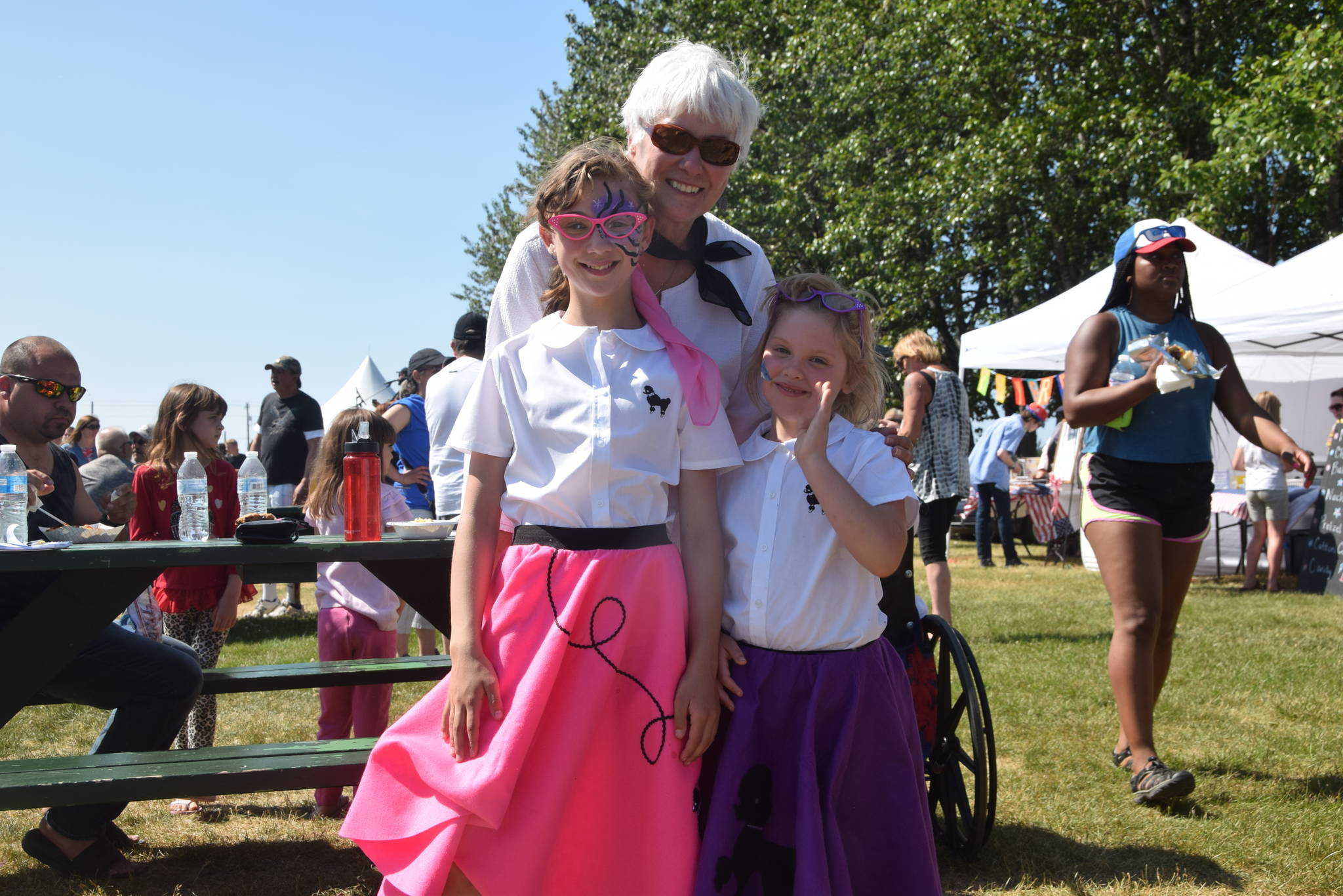 Dorothy Gray and her granddaughters Leah and Eileen Arness smile for the camera at the Kenai Park Strip during the July 4th parade in Kenai, Alaska. (Photo by Brian Mazurek/Peninsula Clarion)