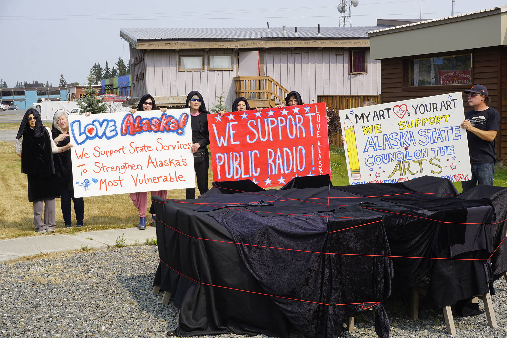 People draped in black hold signs on July 9, 2019, by Sean Derry's public art sculpture in Homer, Alaska, as part of a statewide art intervention to protest Gov. Mike Dunleavy's veto of a $2.8 million state appropriation to the Alaska State Council on the Arts. They also supported a general override of Dunleavy's vetoes that will affect funding for the University of Alaska, public radio and other programs. Derry's sculpture was commissioned as a 1% for art project associated with the remodeling of Pioneer Hall at the Kachemak Bay Campus, Kenai Peninsula College, University of Alaska. The protest was not sanctioned by the college. (Photo by Michael Armstrong/Homer News)